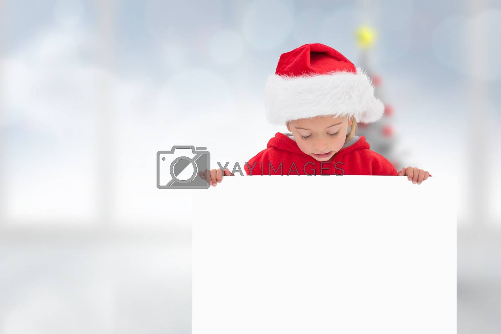 Festive little girl showing poster against blurry christmas tree in room