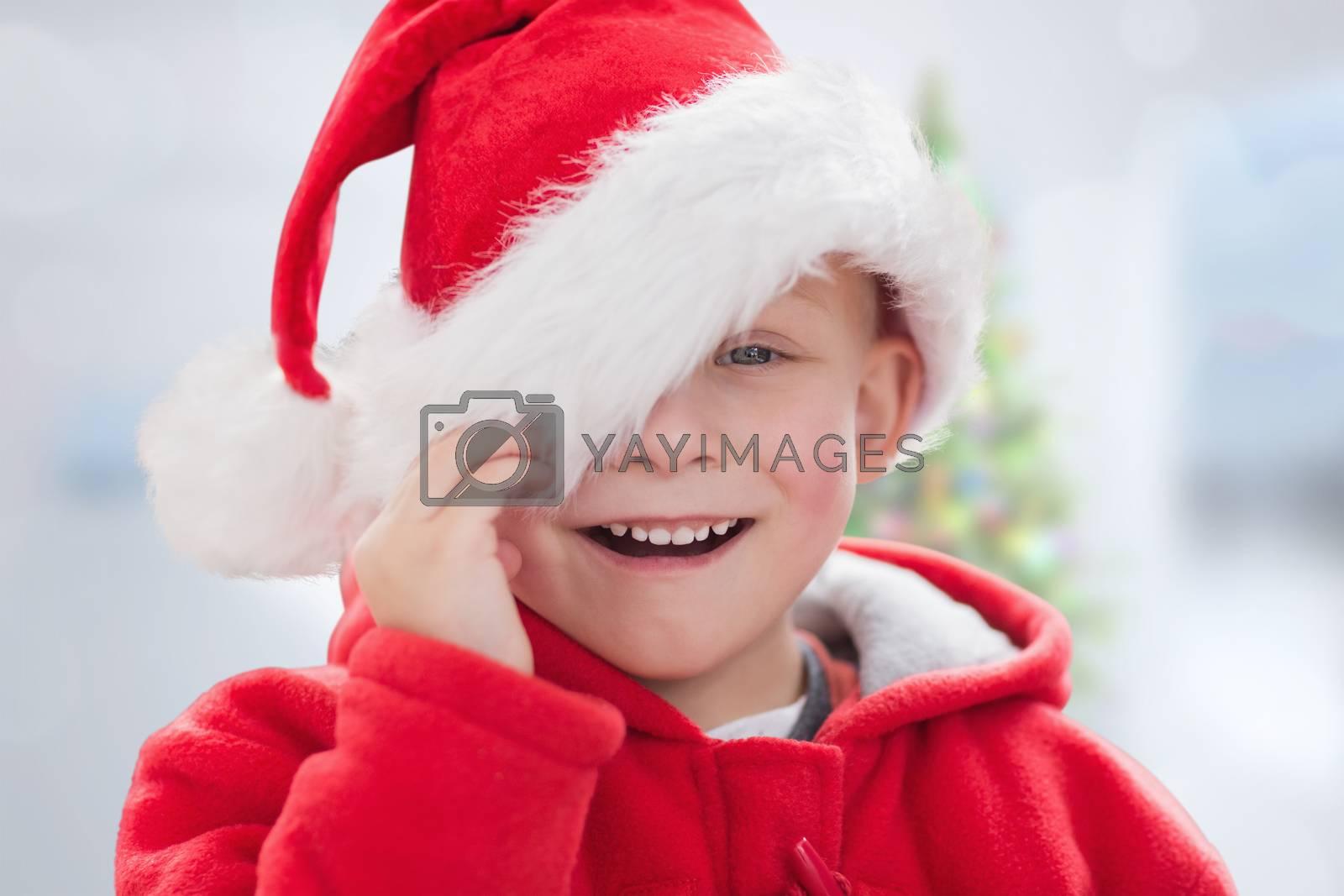 Cute boy in santa hat against blurry christmas tree in room