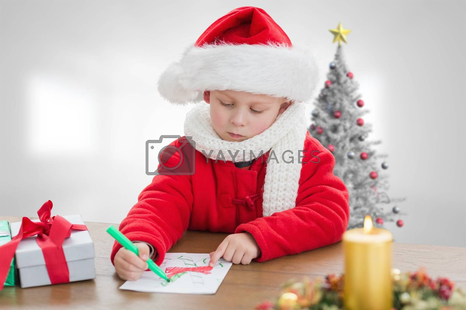 Cute boy drawing festive pictures  against christmas tree in bright room