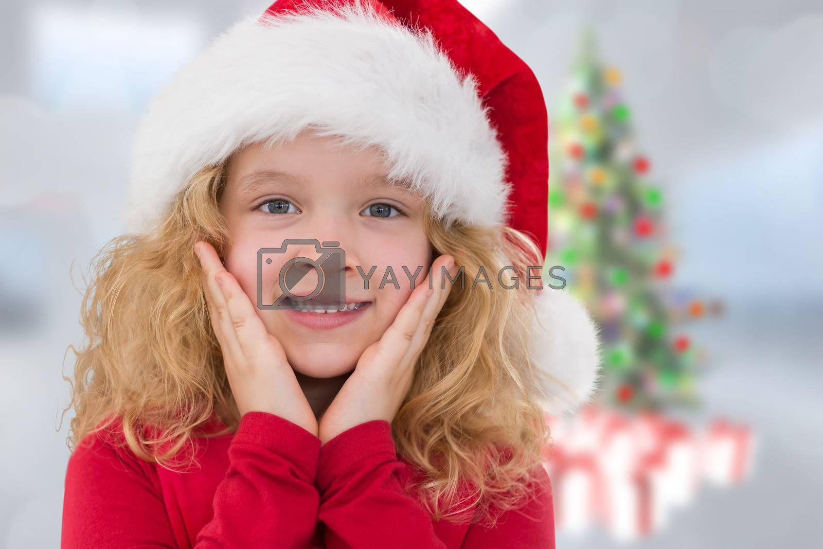 Cute girl in santa hat against blurry christmas tree in room