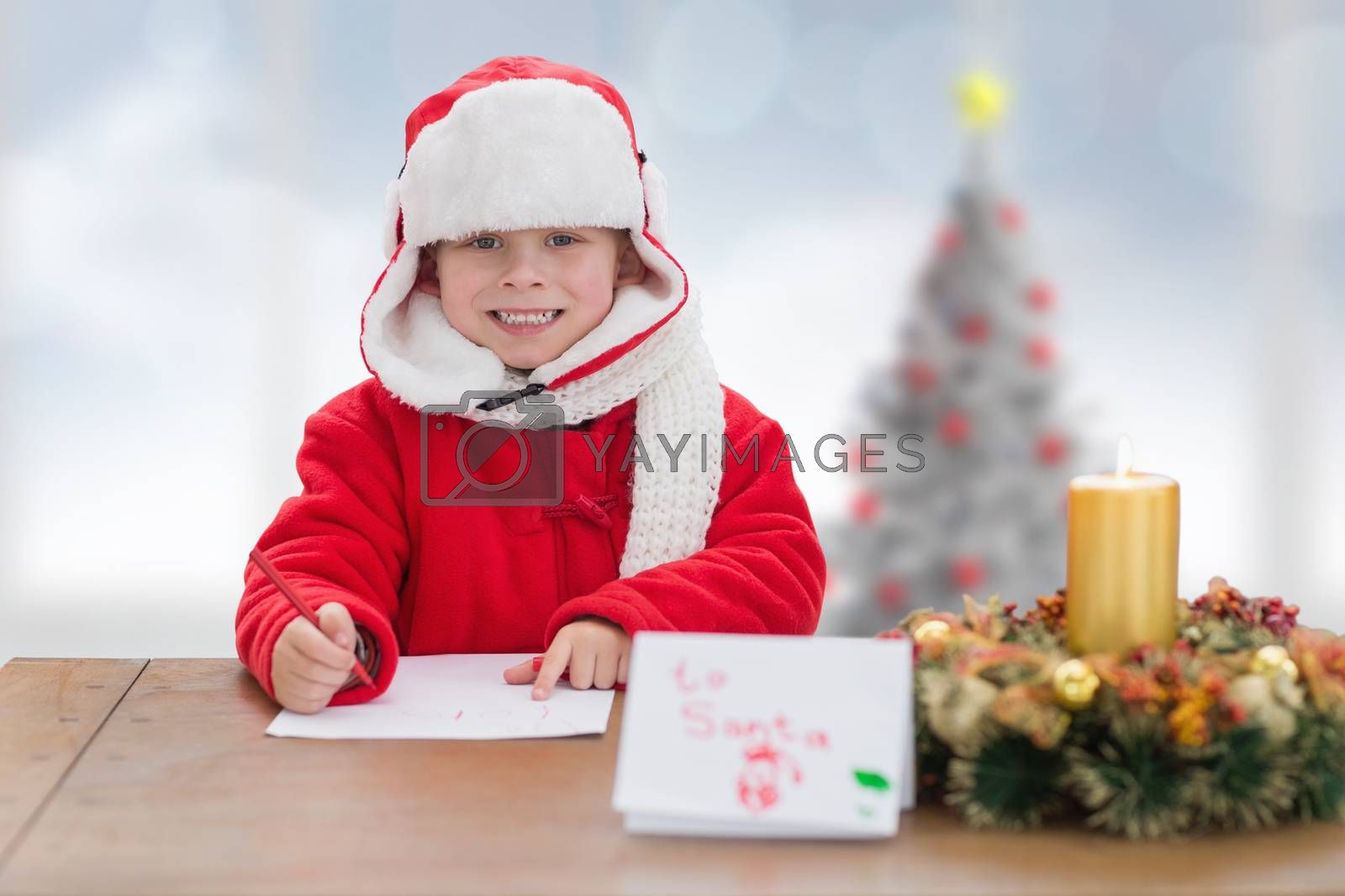 Cute boy drawing festive pictures  against blurry christmas tree in room