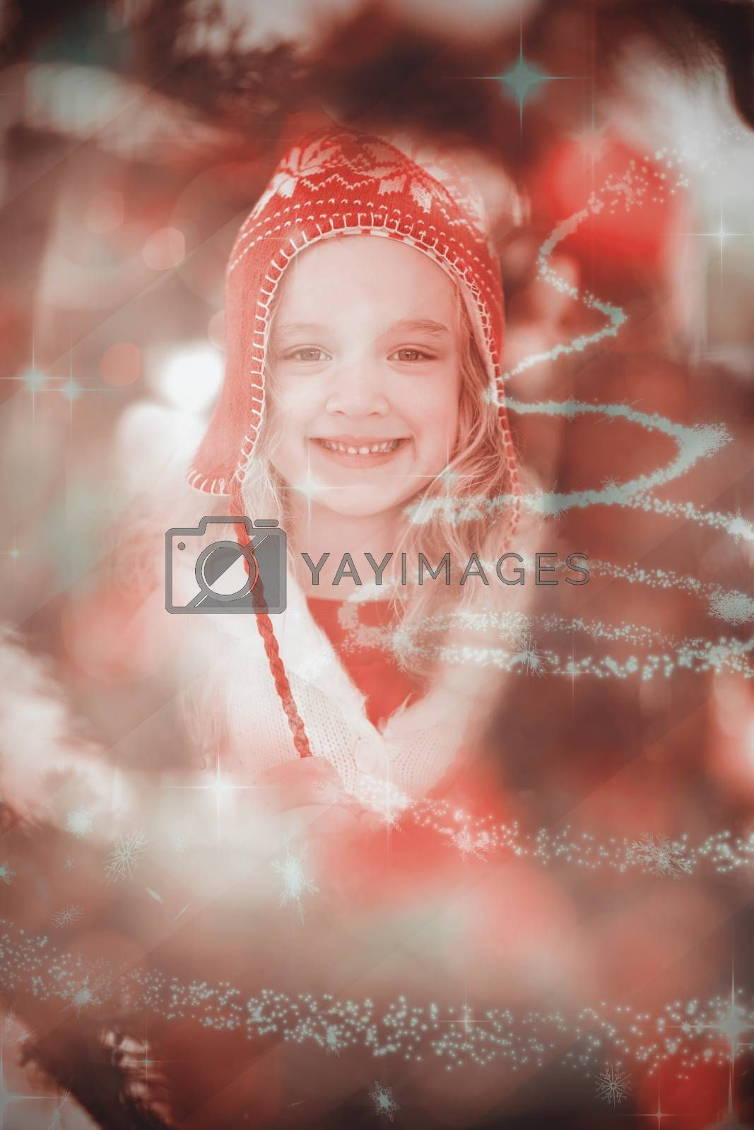 Festive little girl in hat and scarf against glittering christmas tree design