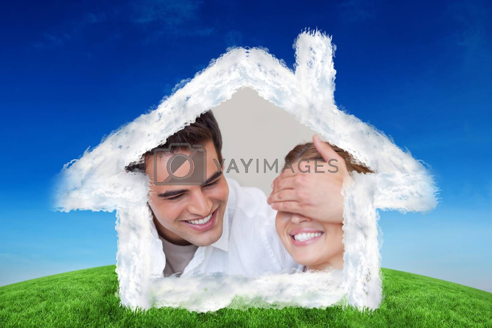 Man covering the eyes of his girlfriend while giving her a present against green hill under blue sky