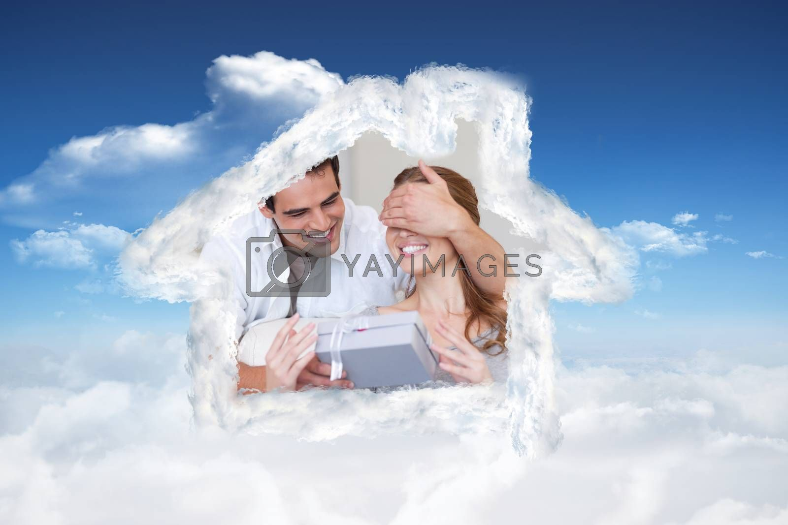 Man covering the eyes of his girlfriend while giving her a present against bright blue sky with clouds