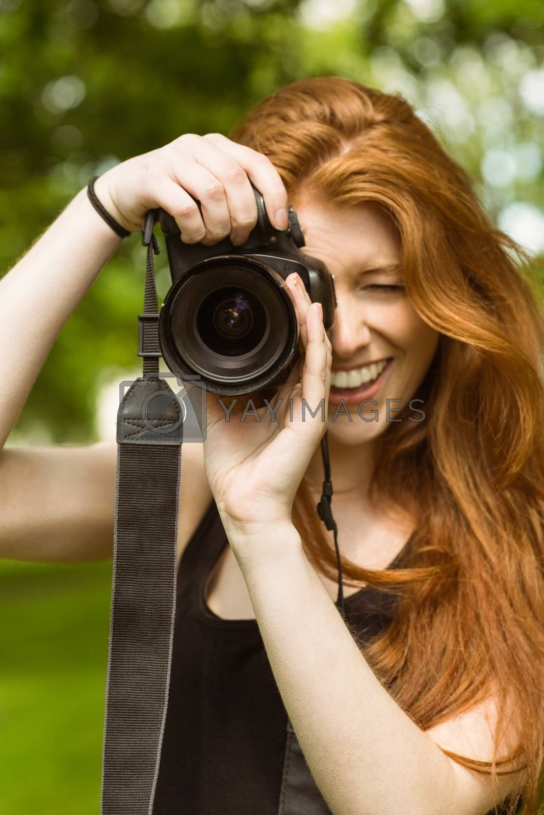 Beautiful female photographer at park by Wavebreakmedia