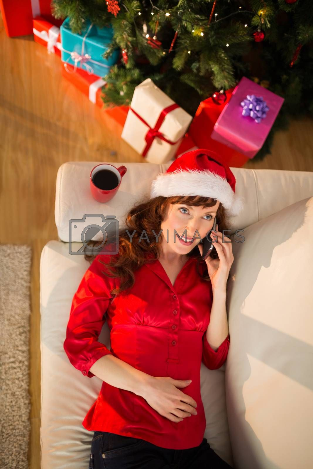 Smiling redhead on the phone at christmas at home in the living room