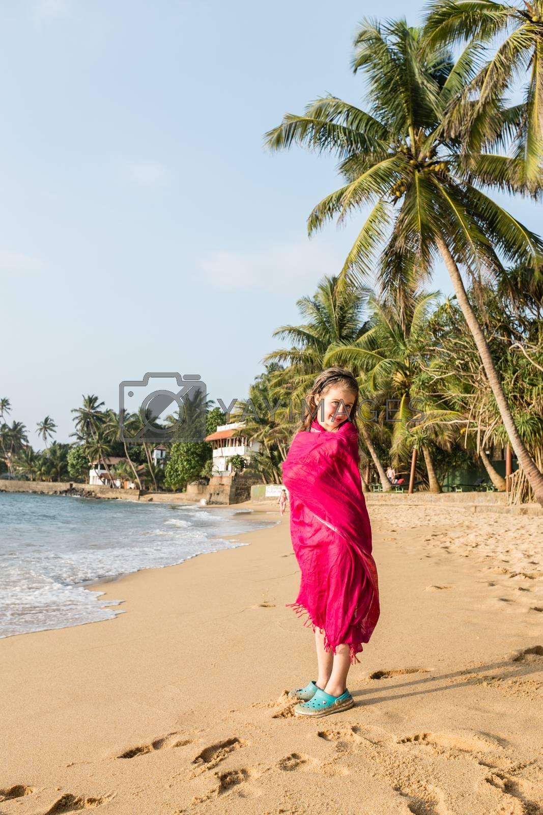 Little girl in pareo at ocean beach, Beruwala, Sri Lanka