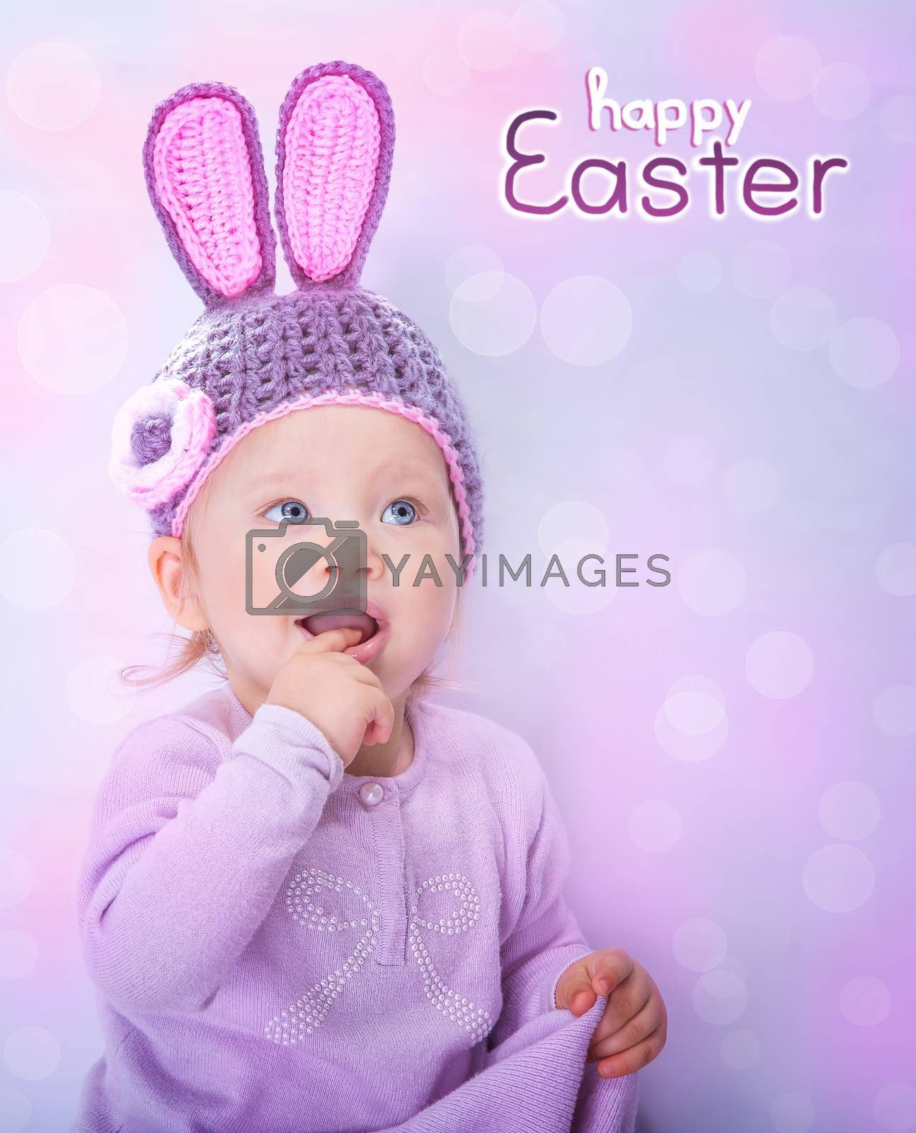 Portrait of happy adorable child wearing cute knitted hat with rabbit ears on pink blur background, greeting card with text space, happy Easter bunny costume