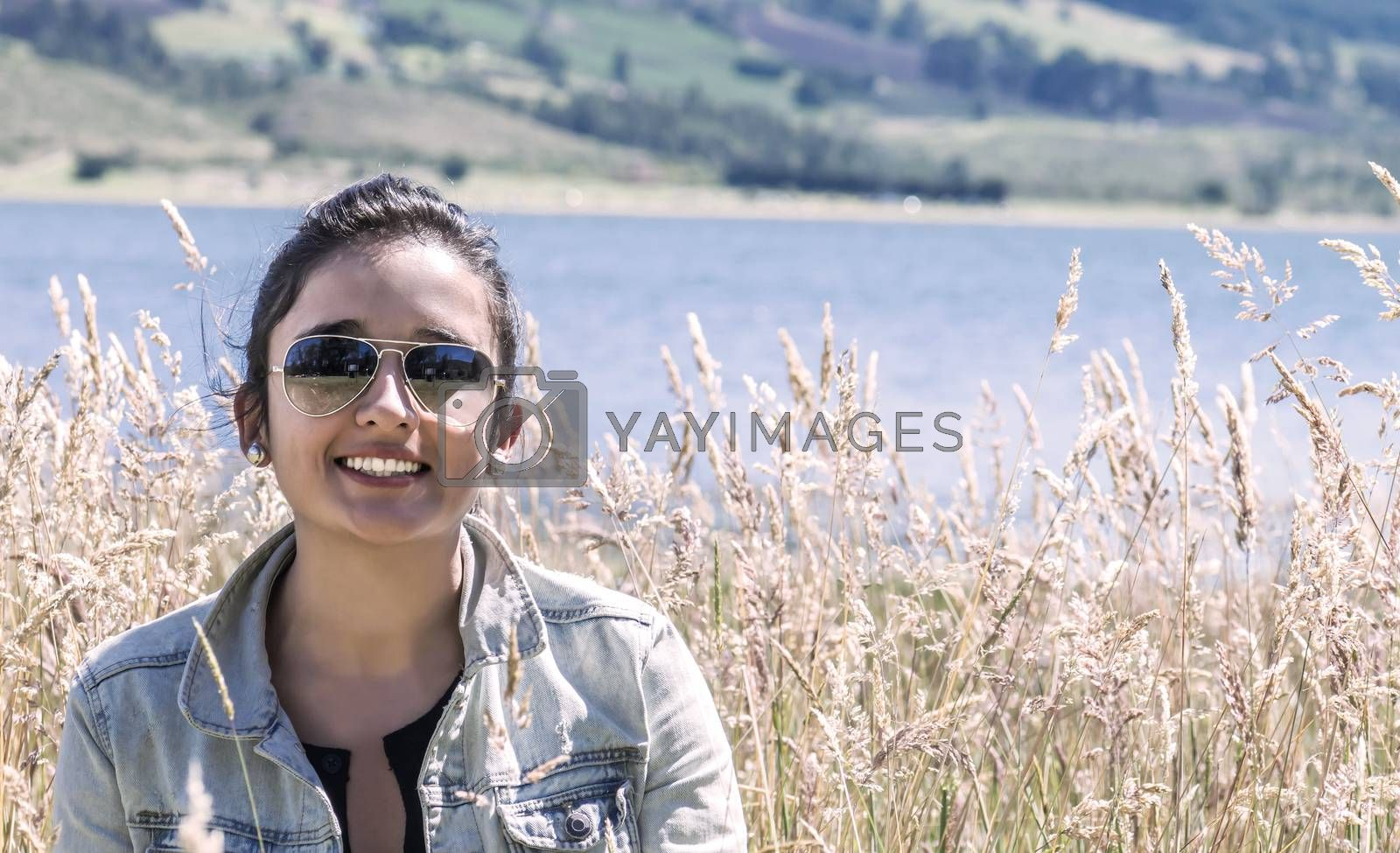 Young latin woman into a golden grass field smiling