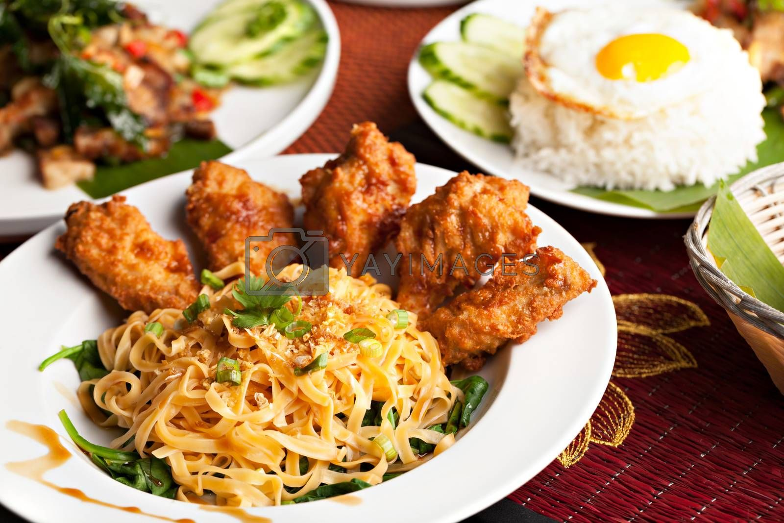 Thai style fried siracha chicken wings on a round white plate with egg noodles and spinach.