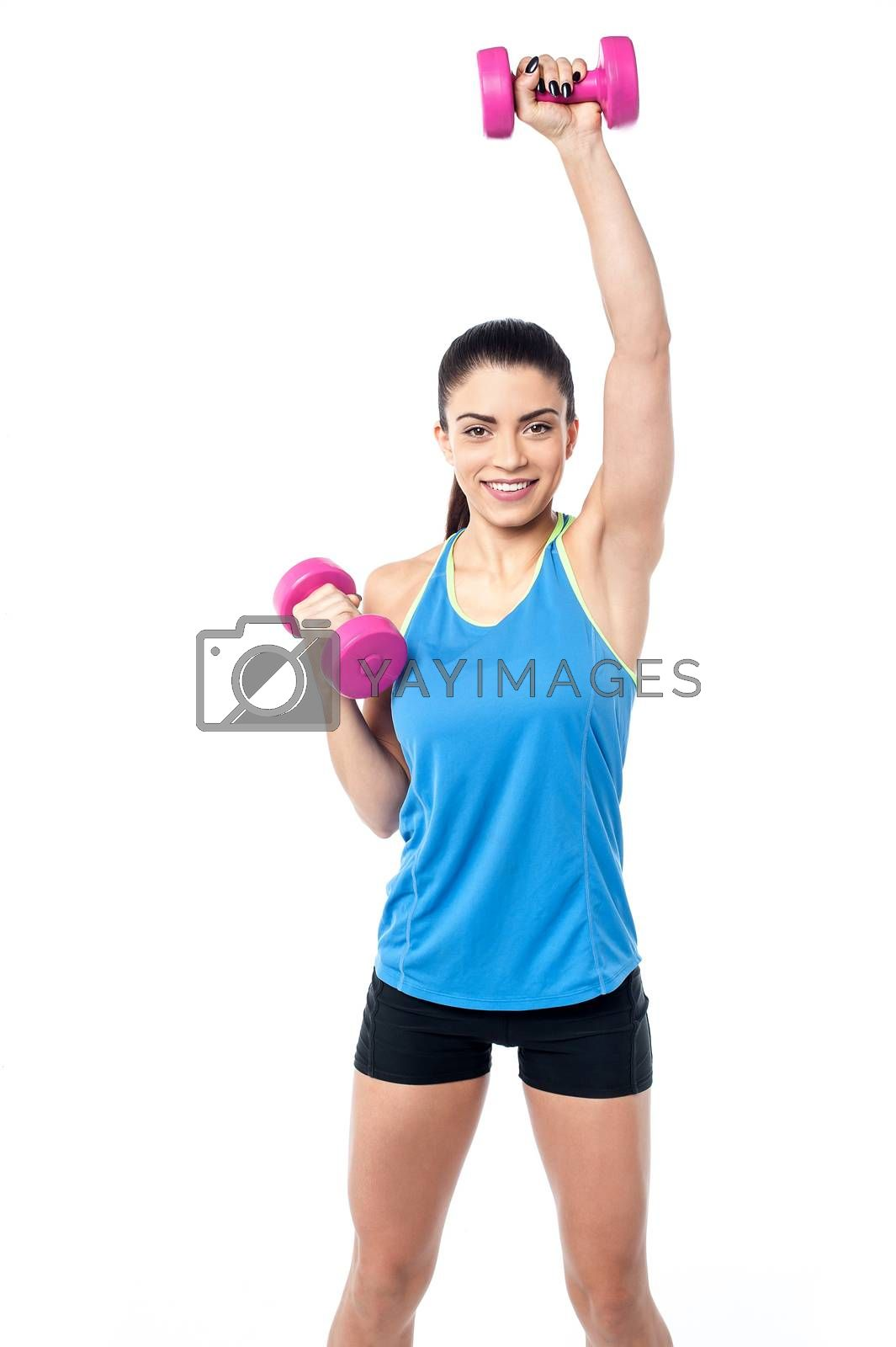 Young fitness woman working out with dumbbells