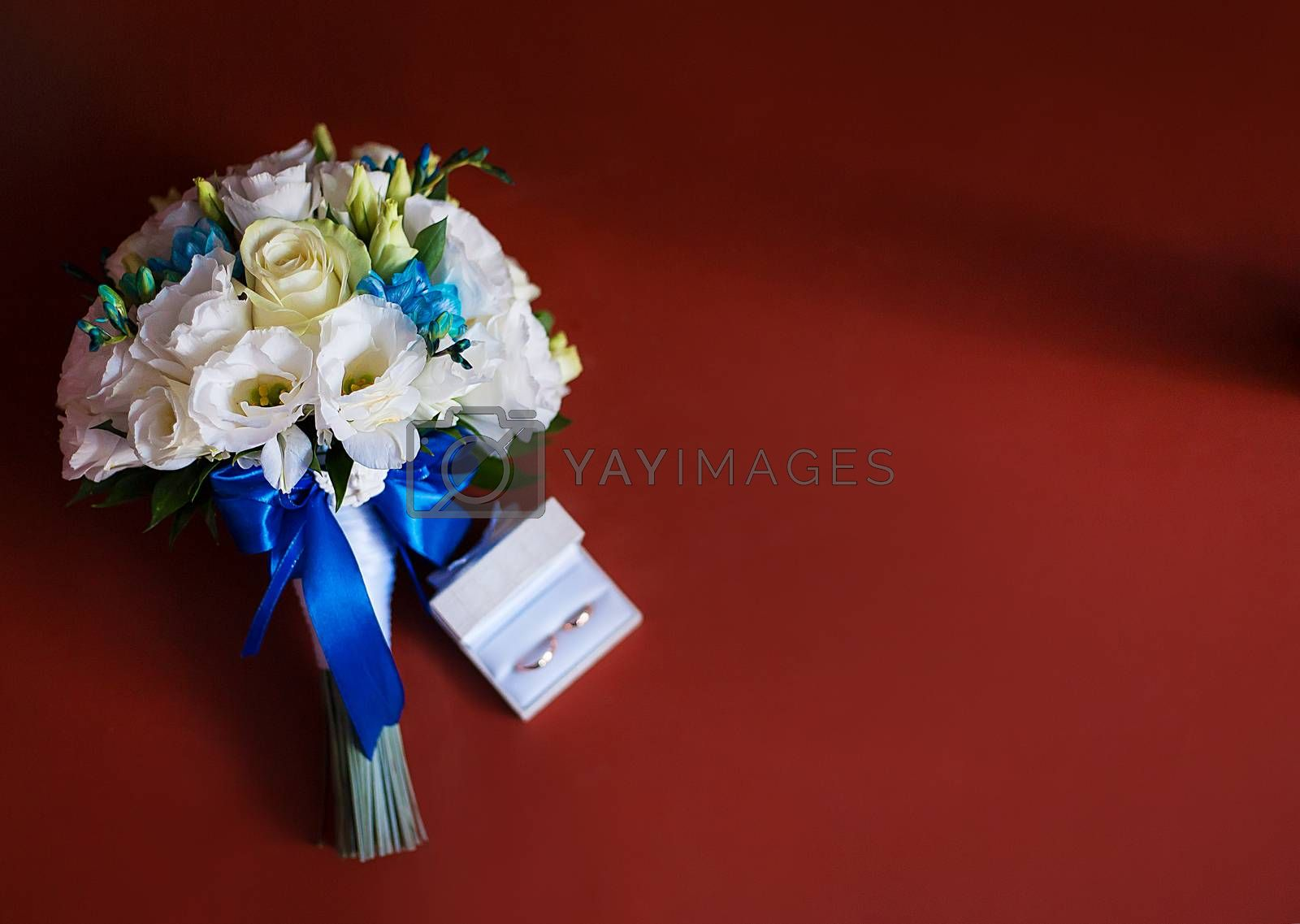 Royalty free image of Wedding rings with a bridal bouquet of white roses by sfinks