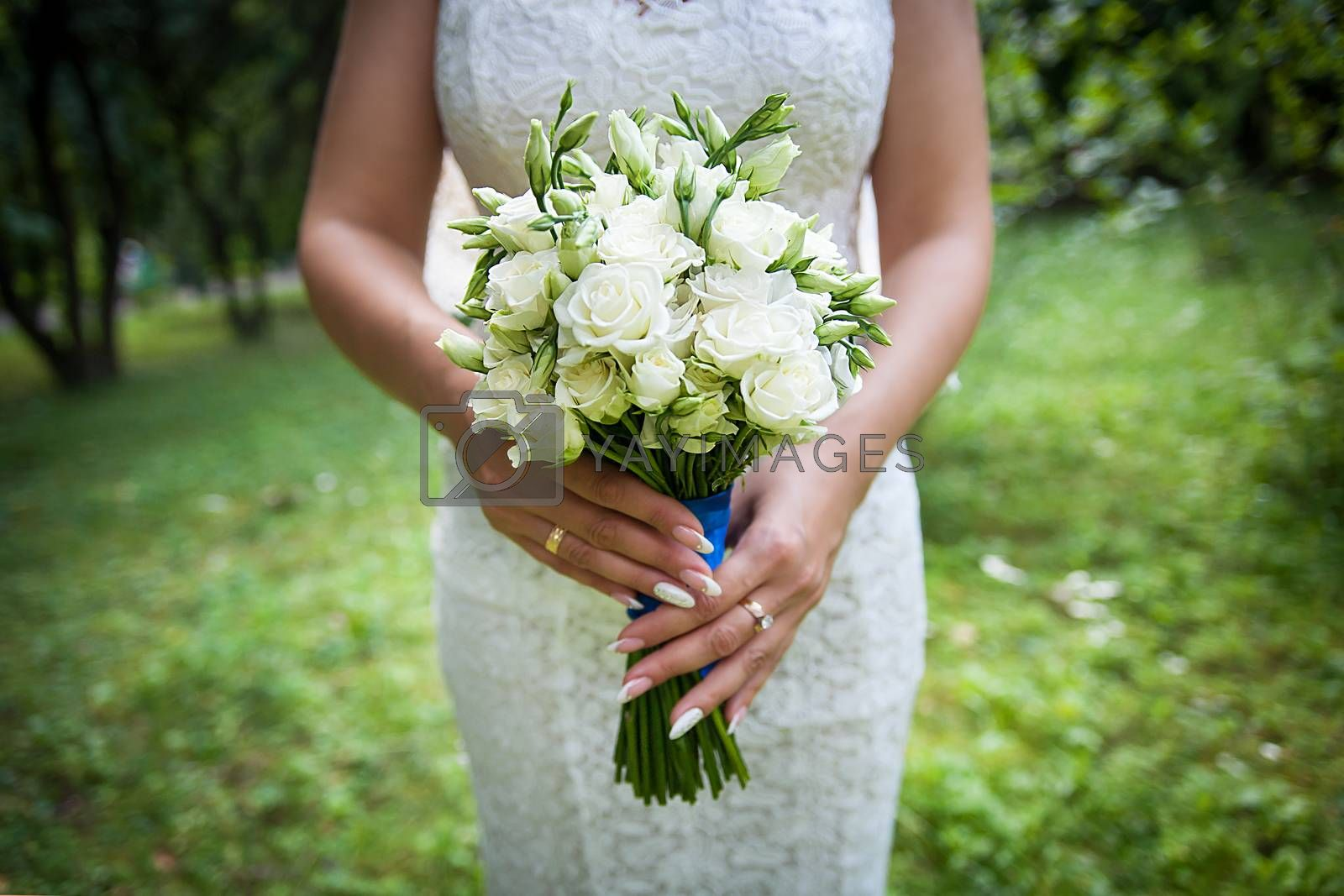 Royalty free image of Beautiful wedding bouquet in hands of the bride by sfinks