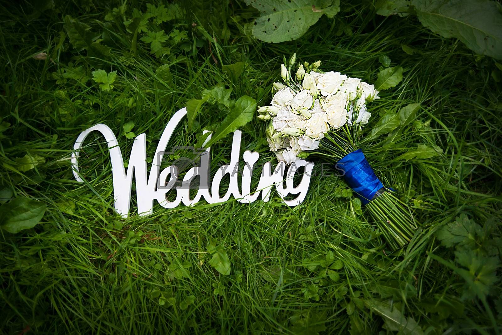 Royalty free image of wedding letters with white flowers on grass by sfinks