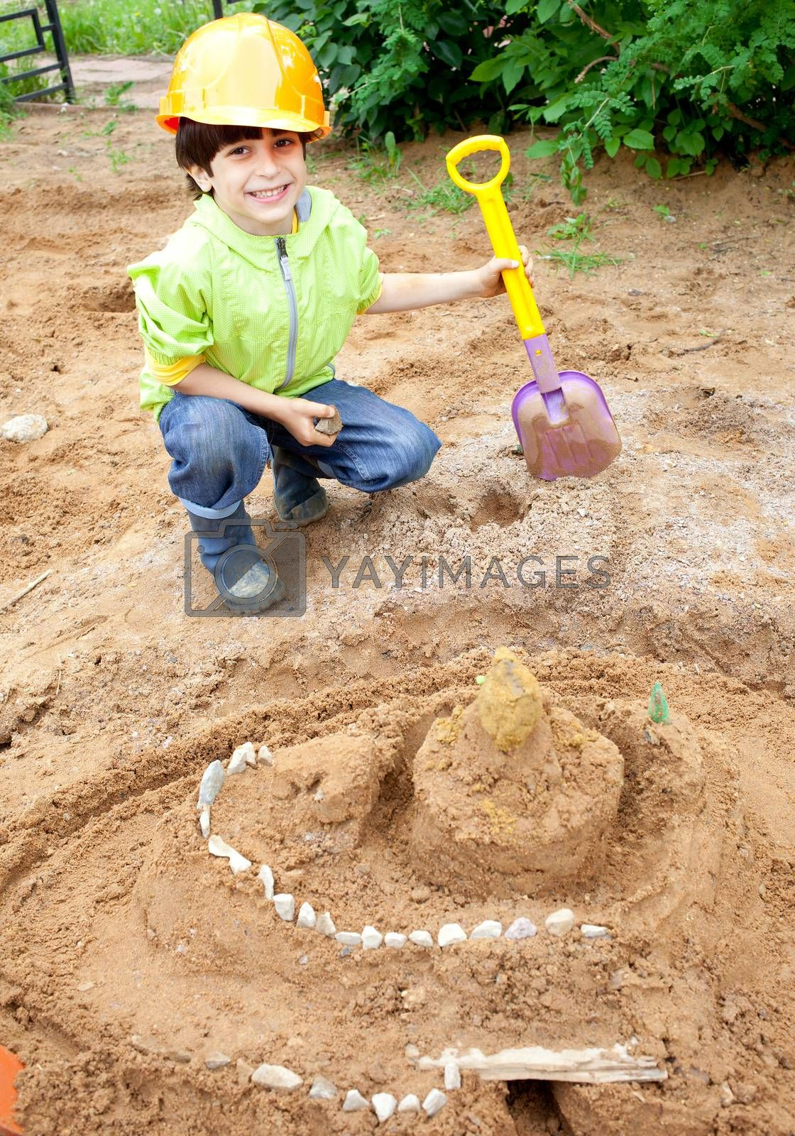 boy builder in a protective helmet and a shovel near the sand castle