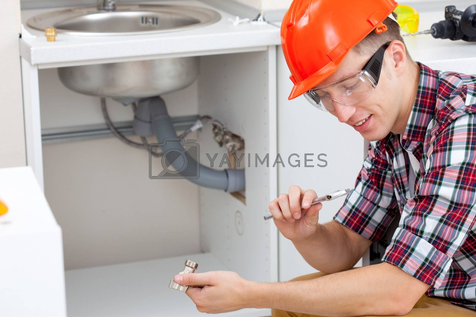 smiling mechanic adjusts the key near the kitchen sink