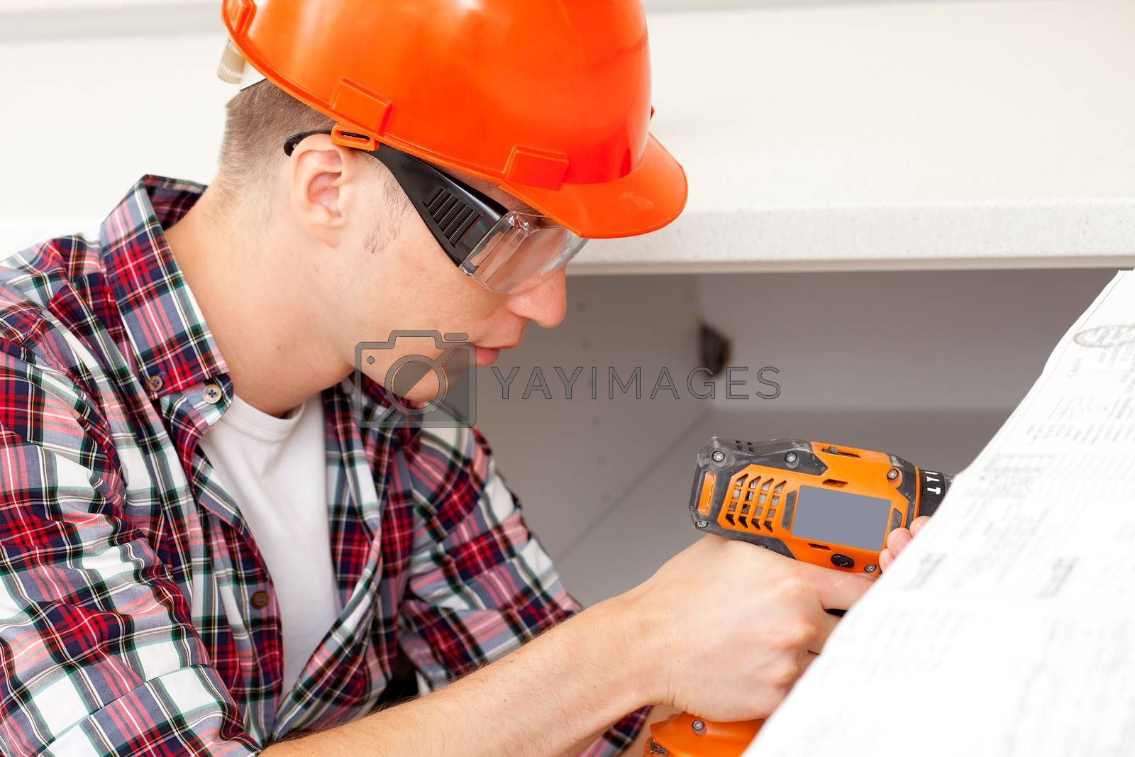 repairman at doors installation with electric drill into interior kitchen furniture