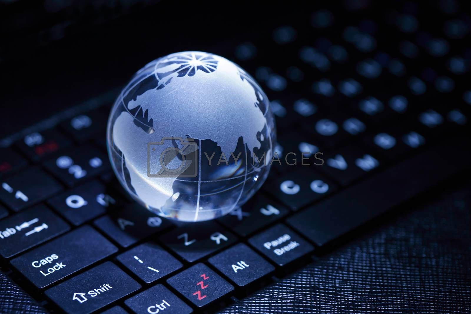 Internet concept. Closeup of glass globe on laptop keyboard