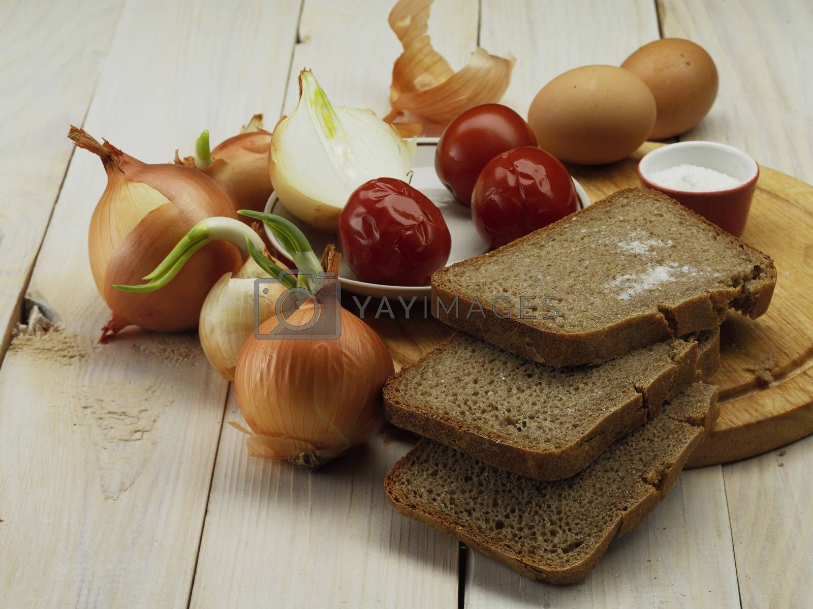 root of onion and bread on wooden board