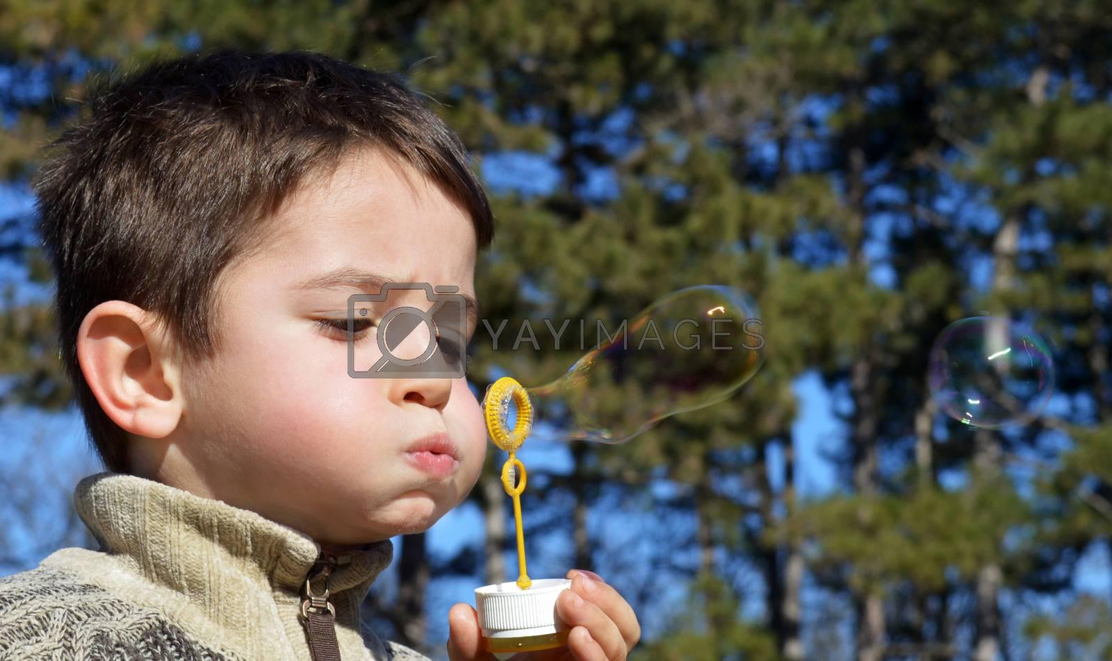 Cute boy makes soap bubbles