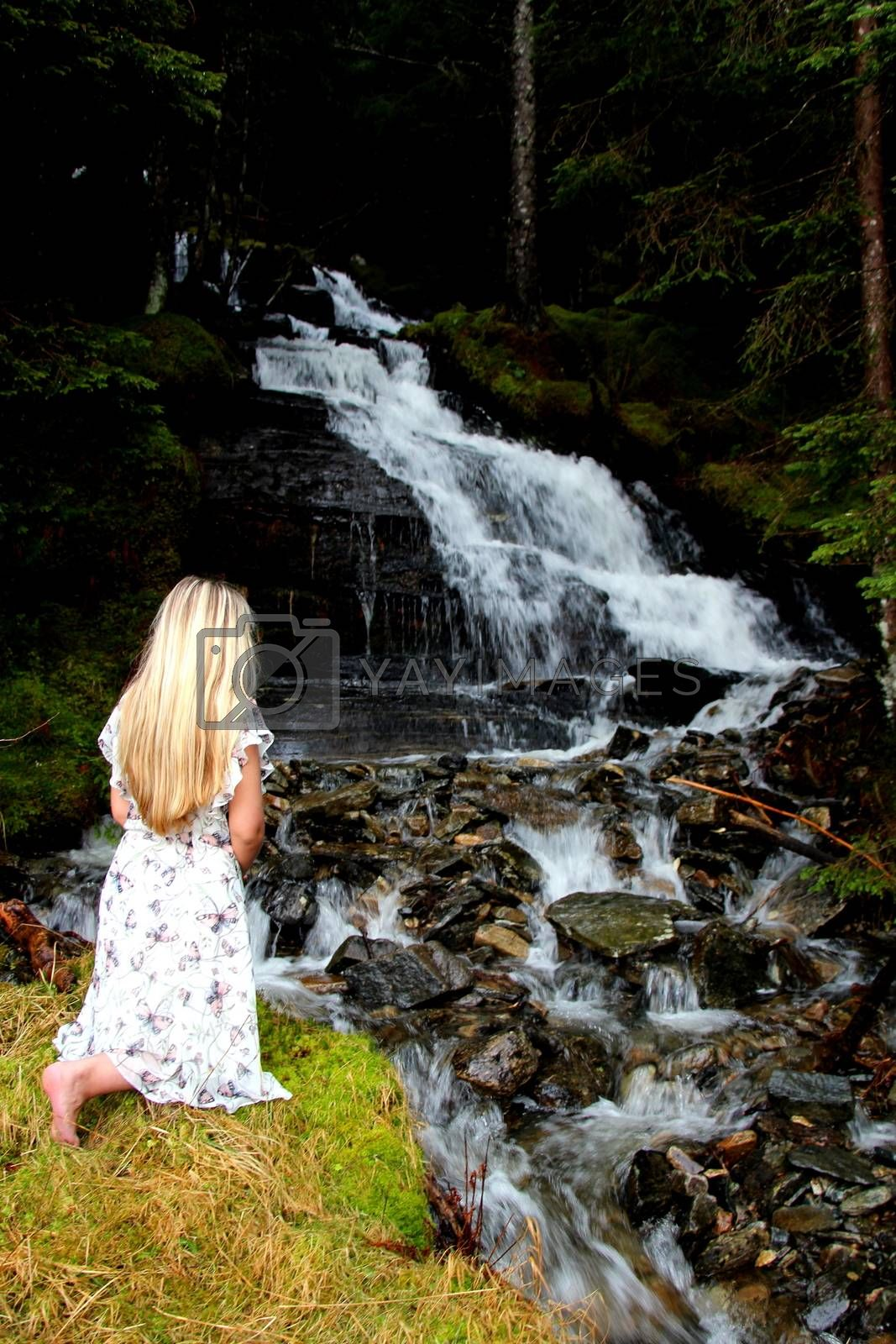 Praying girl sitting at a waterfall