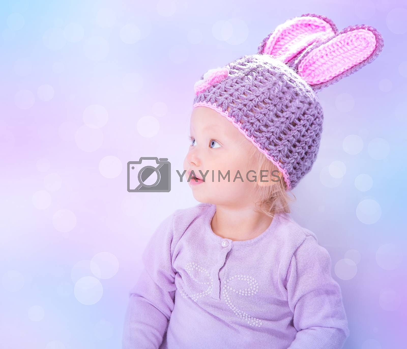 Portrait of cute Easter bunny isolated on blur background, sweet little baby wearing purple hat with rabbit ears, celebrating religious holiday