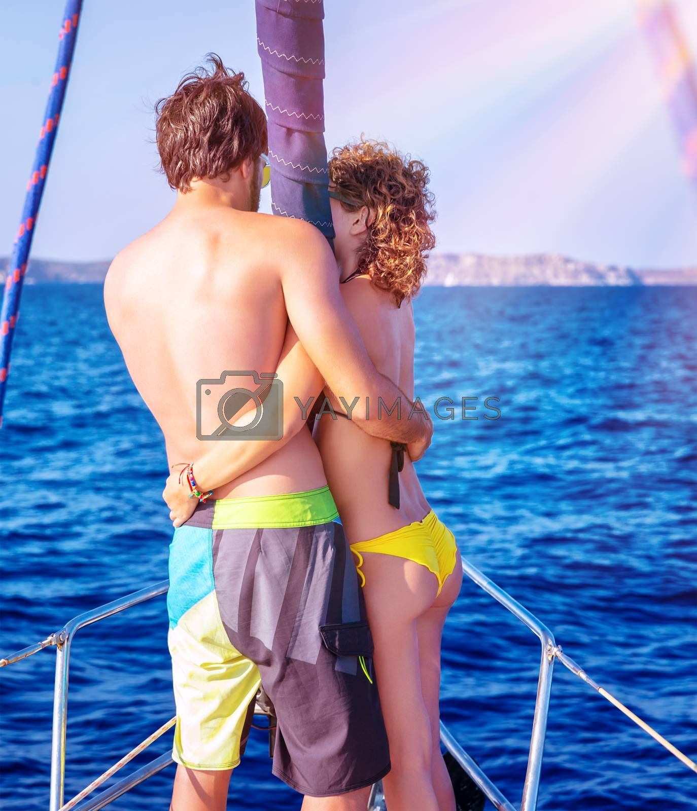 Back side of happy loving couple standing on the mast of luxury sail boat and hugging, enjoying sea view, summer vacation in love