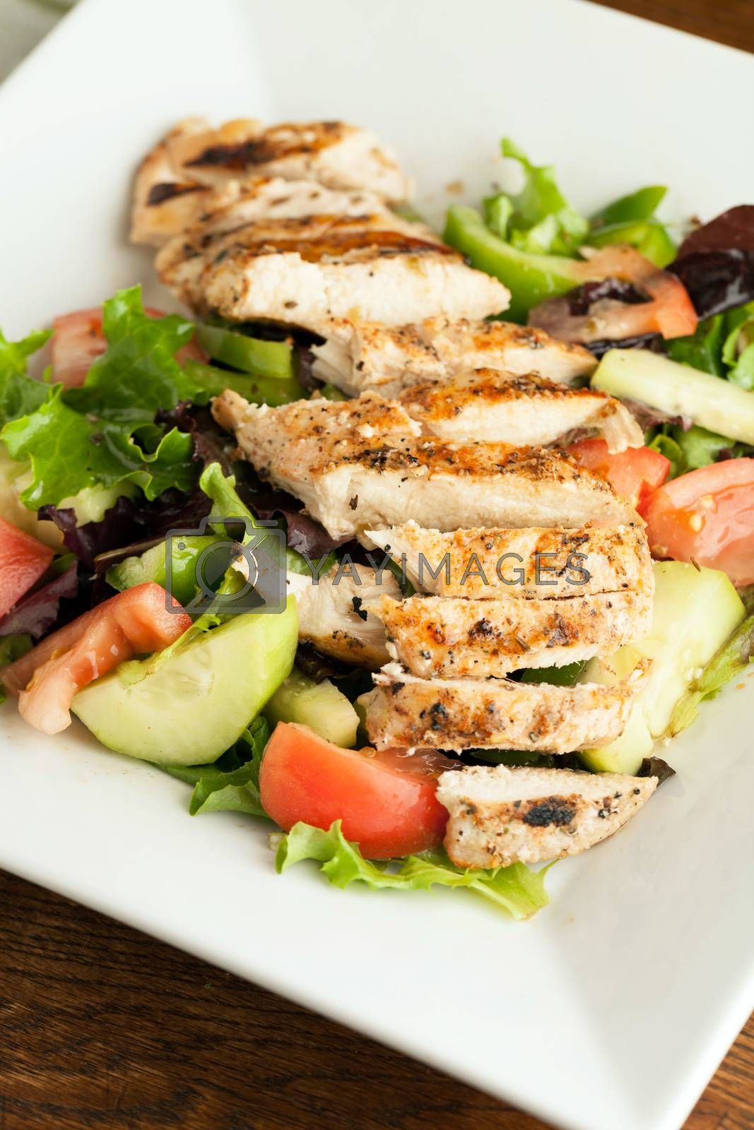 Freshly prepared grilled chicken chef style salad with tomato cucumber green pepper and romaine lettuce.