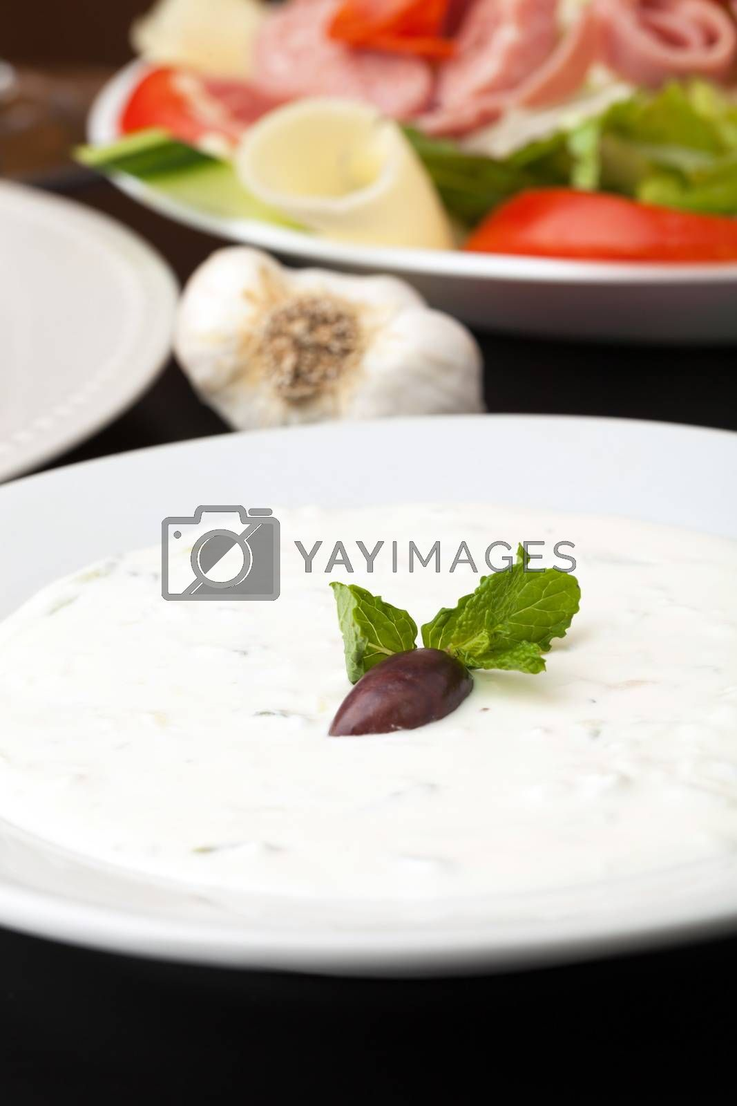 Traditional Gyro sandwich tzatziki sauce garnished with a kalamata olive and mint. Shallow depth of field.