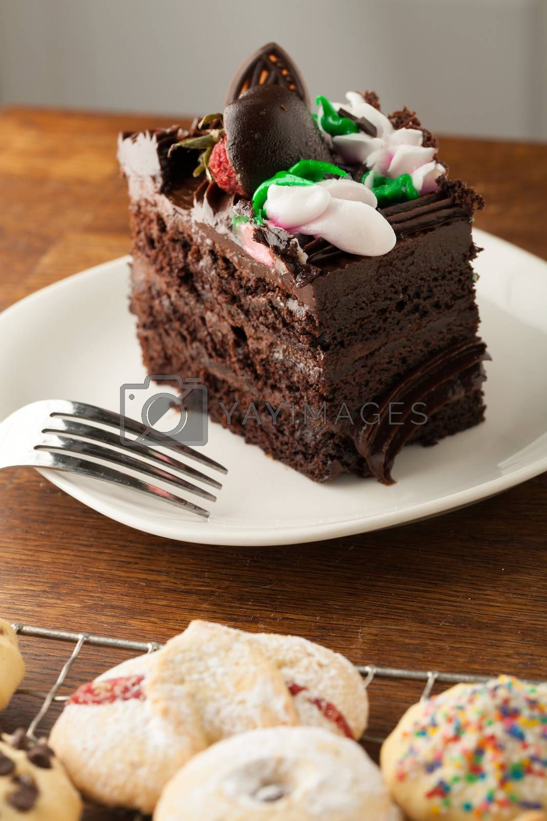 Decadent slice of chocolate cake with iced flowers and chocolate covered strawberries on a plate with a fork.