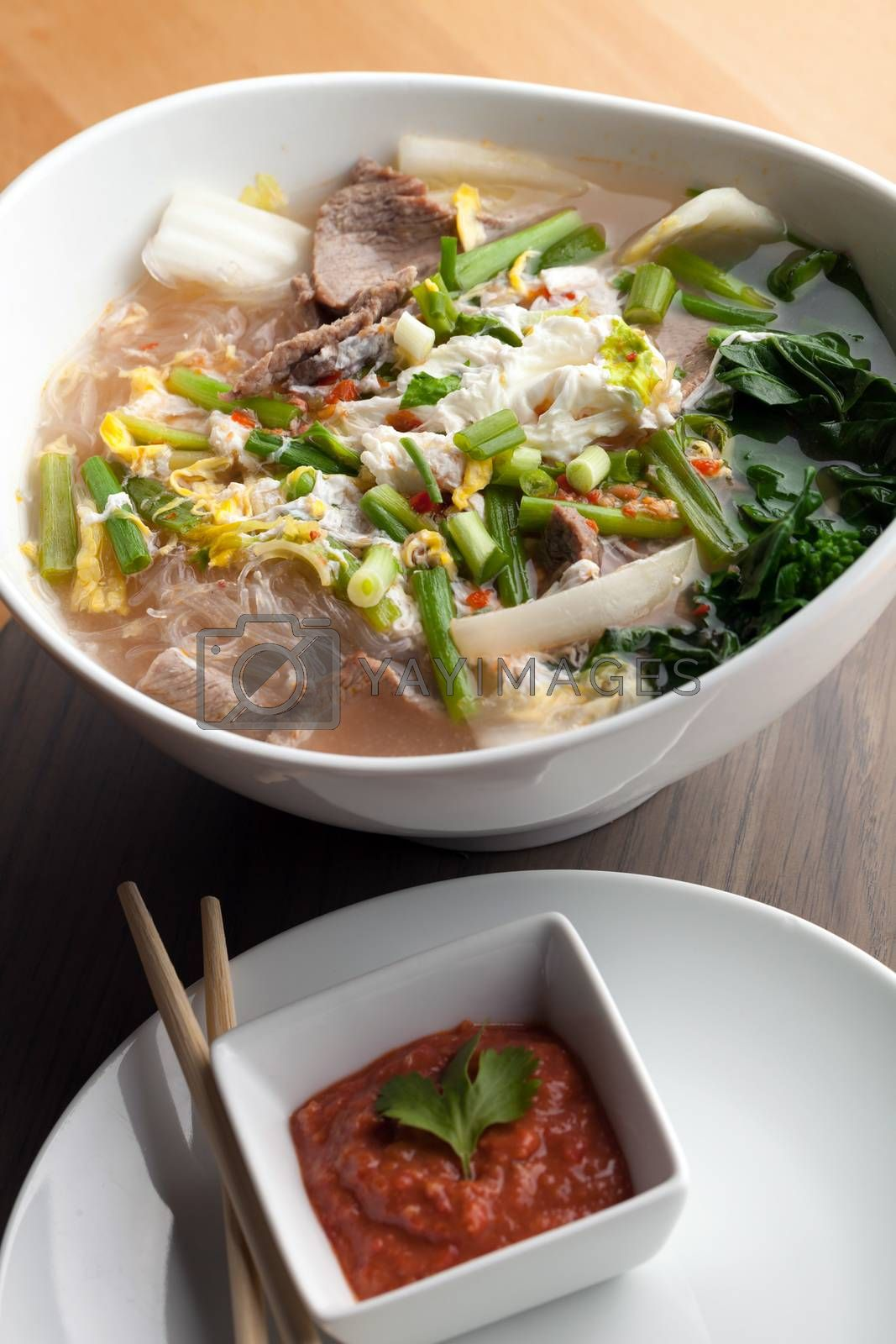 Closeup of some Thai pho style soup with beef and clear rice noodles. Sriracha dipping sauce.