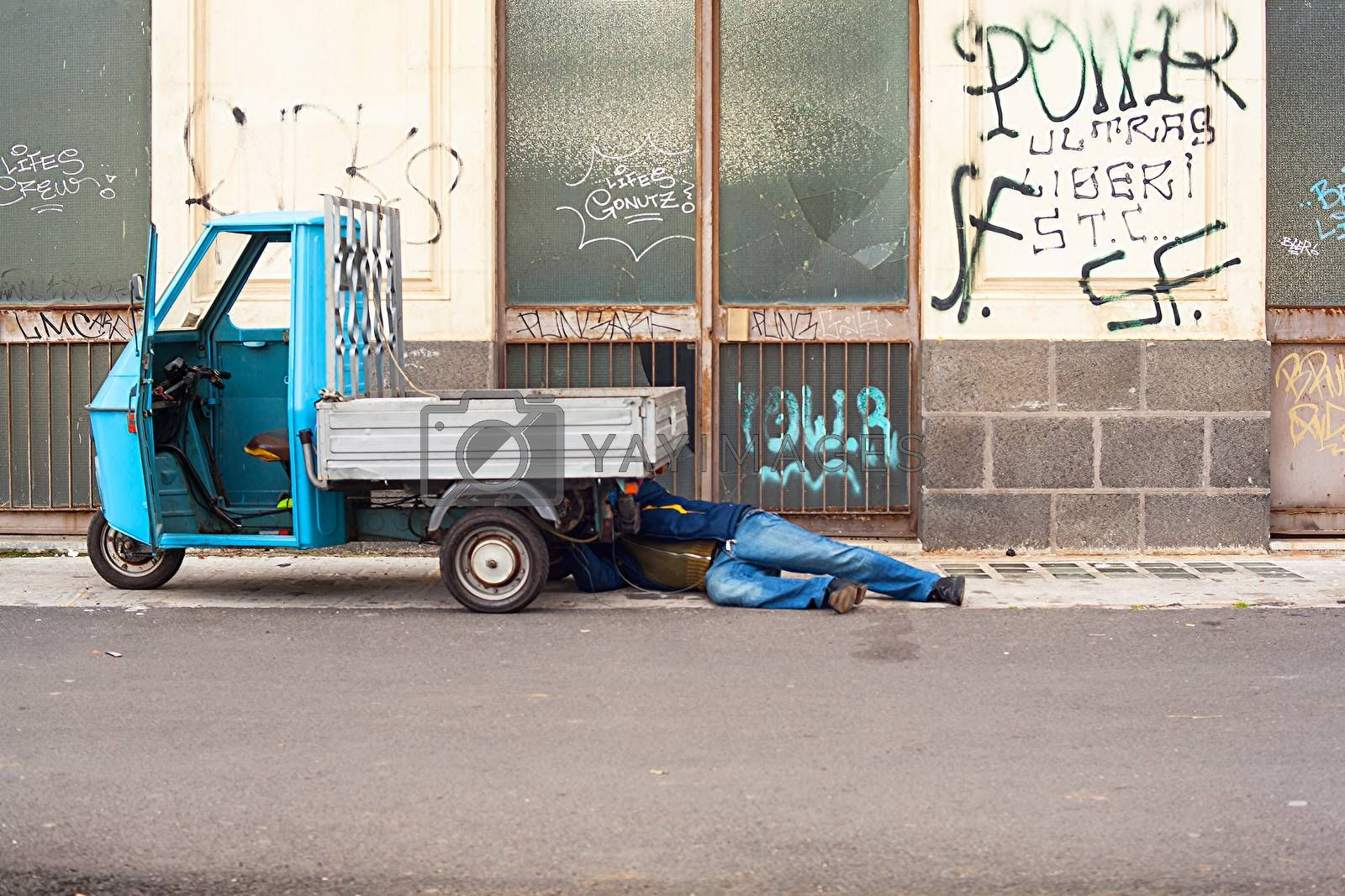 CATANIA, ITALY - DECEMBER, 15: Man under the hood of his three-wheeled on December 15, 2014