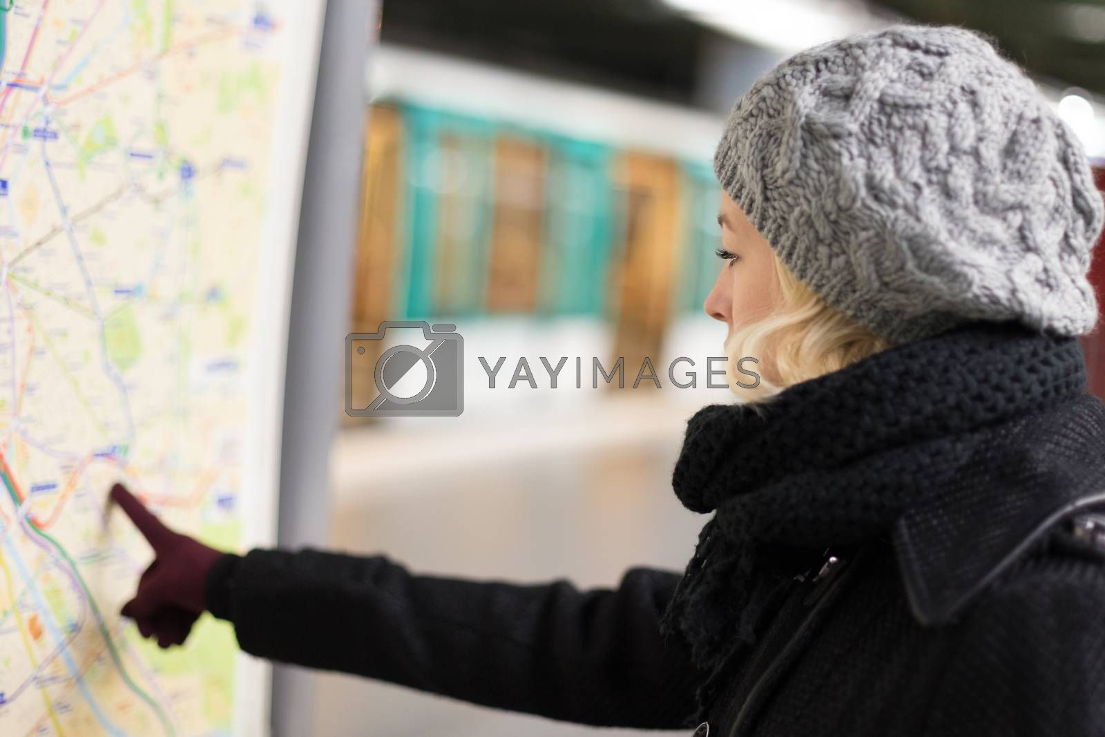 Casually dressed woman wearing winter coat, orientating herself with public transport map panel, pointing on her final destination. Urban transport.