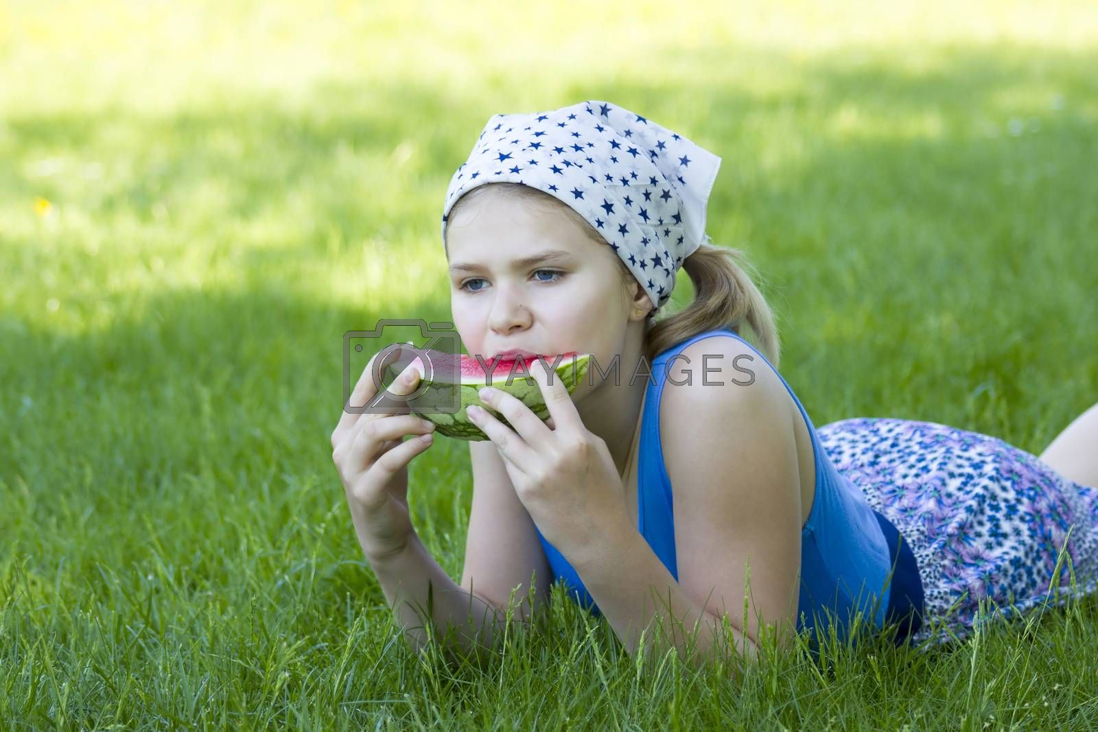 cute little girl eating watermelon on the grass
