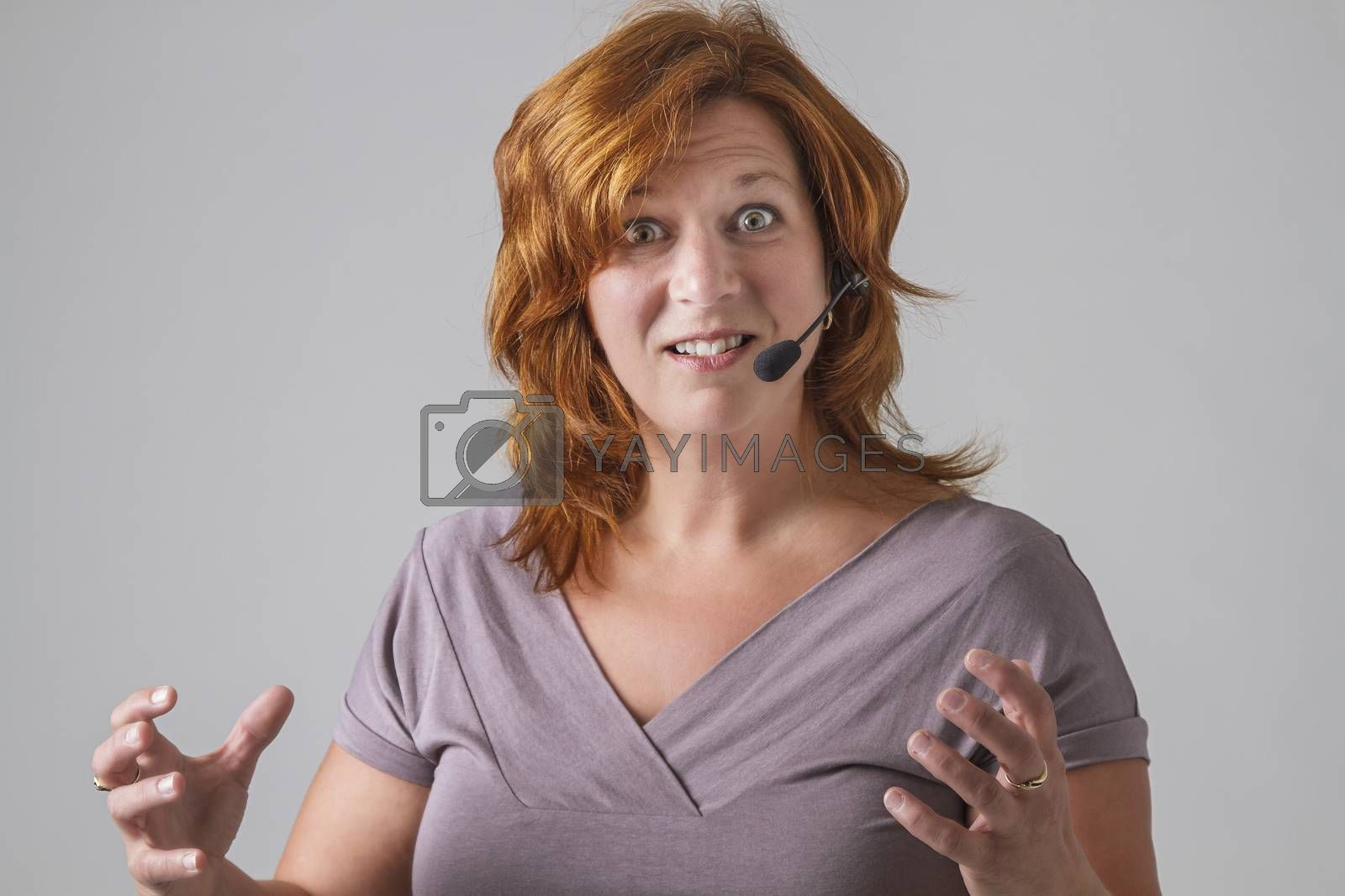 red hair female phone agent with headset with angry expression