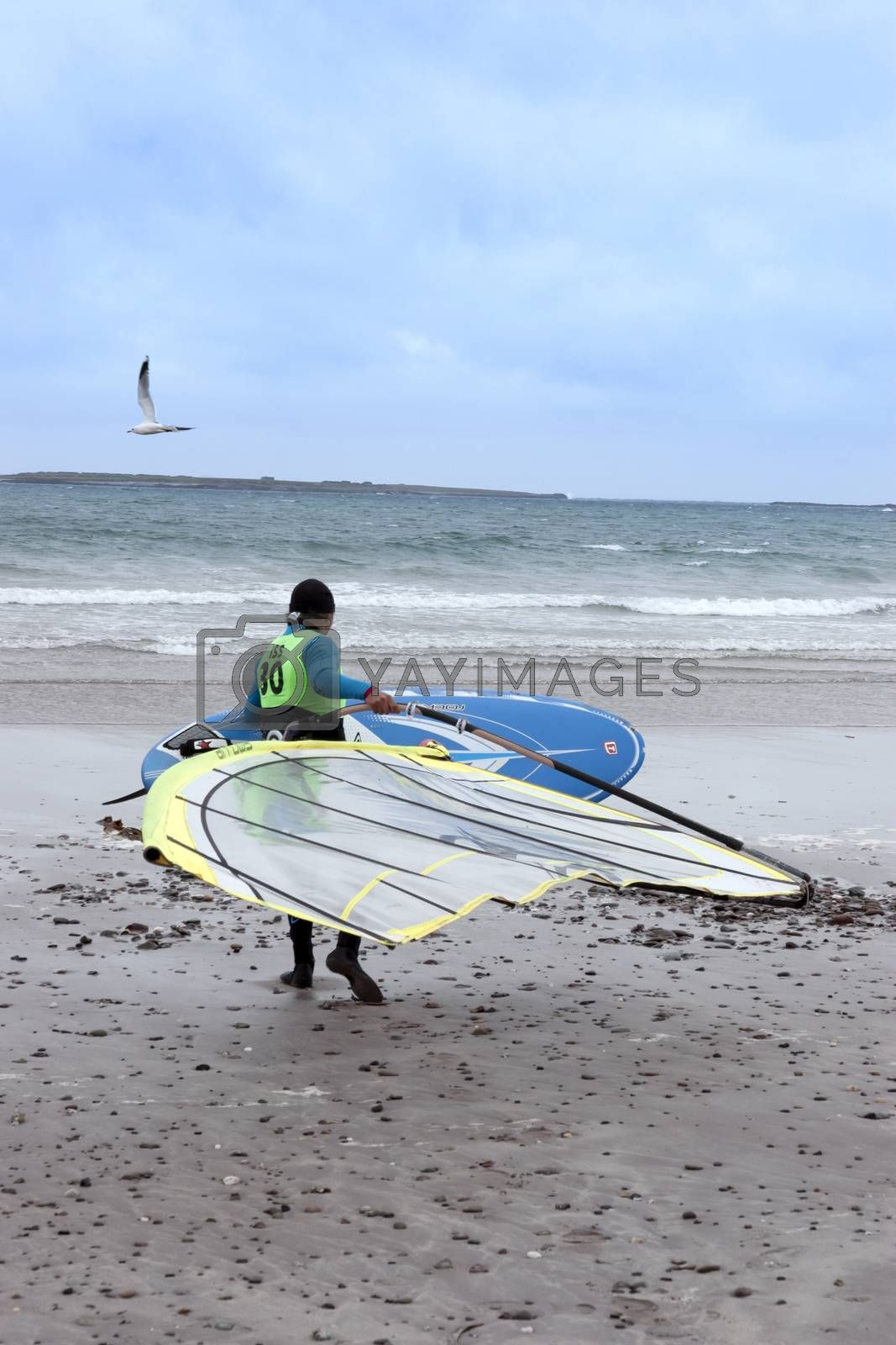 windsurfer getting ready to surf on the beach in the maharees county kerry ireland