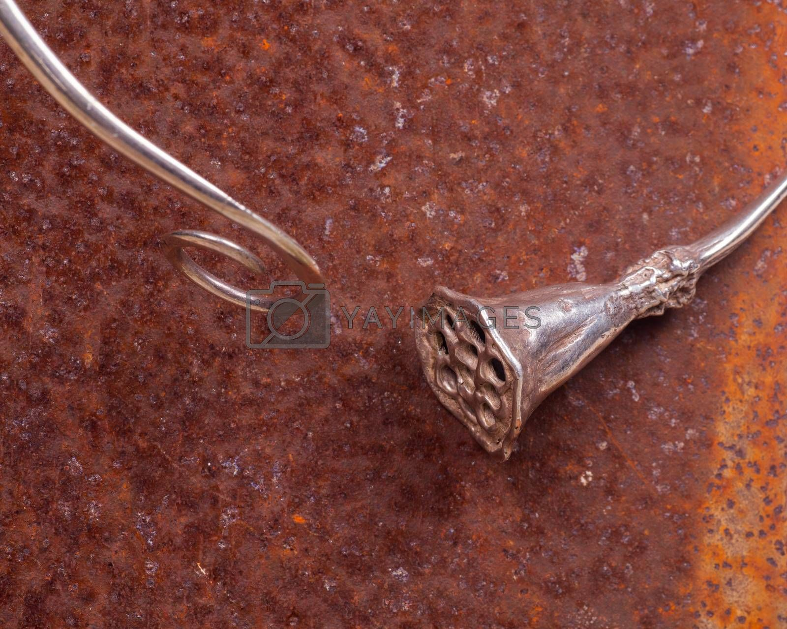 Close up of silver necklace on rusty iron, manufactured by Ornella Salamone