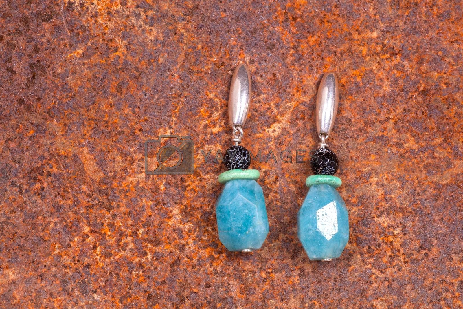 Close up of chalcedony earrings on rusty iron, manufactured by Ornella Salamone