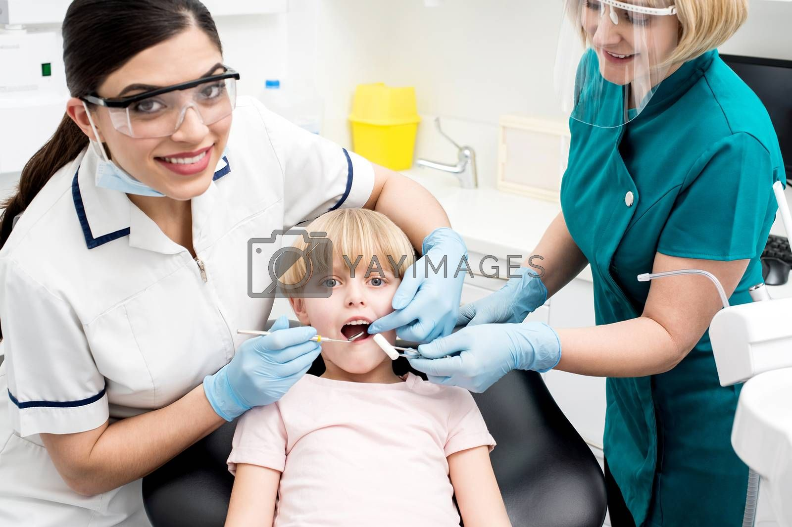 Dentist and nurse are curing a little girl patient