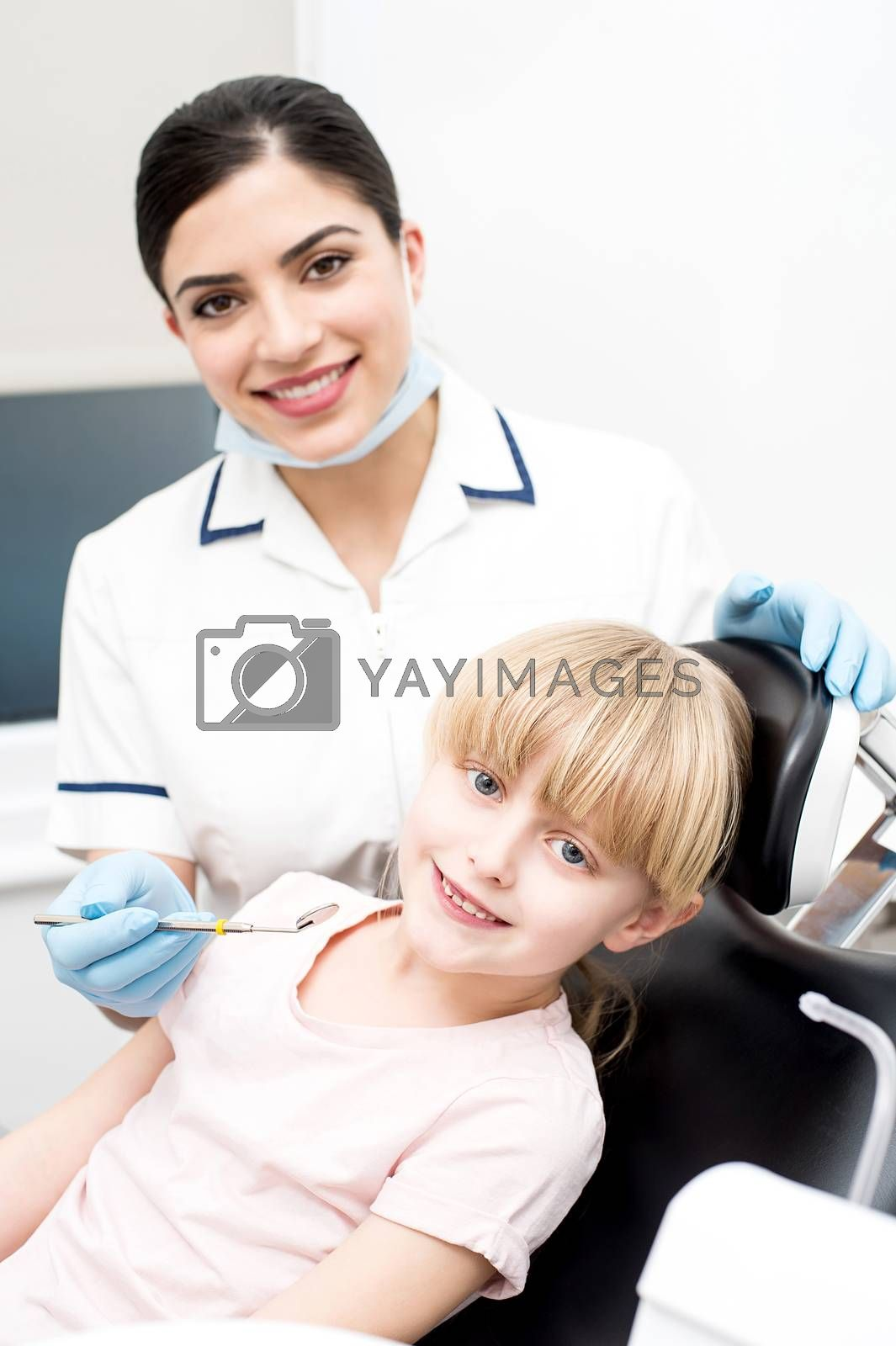 Dental assistant and little girl looking at camera