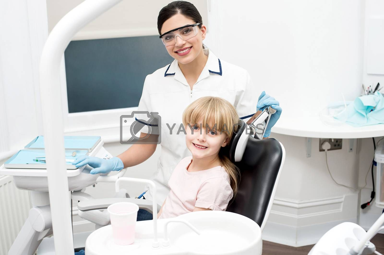 Smiling dentist with little girl after her check up