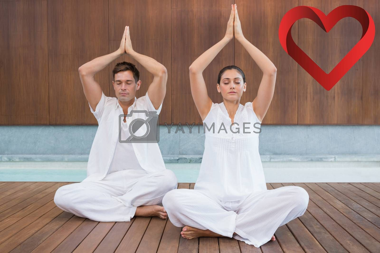 Attractive couple in white sitting in lotus pose with hands together against heart