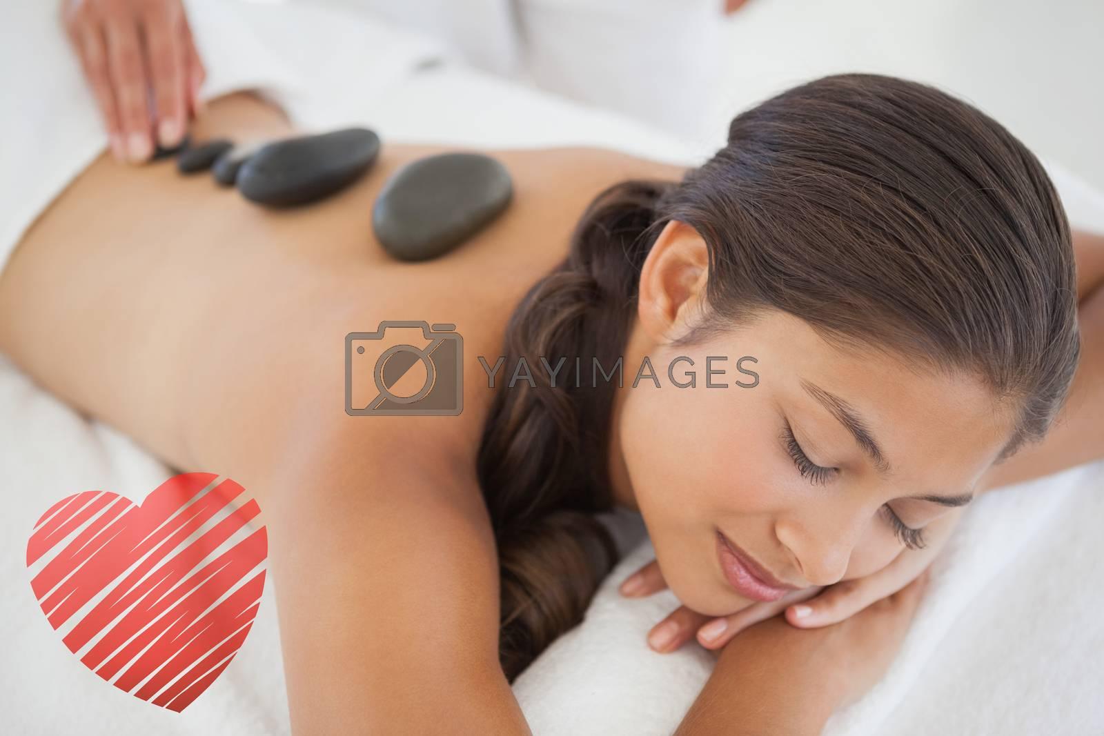 Beautiful brunette enjoying a hot stone massage against red heart