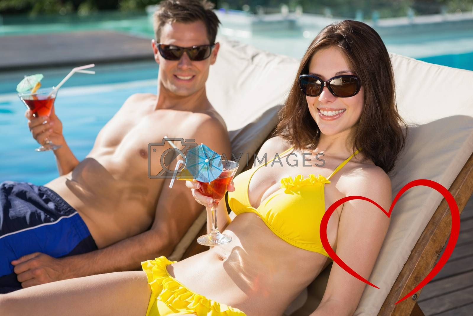 Smiling couple with drinks sitting by swimming pool against heart