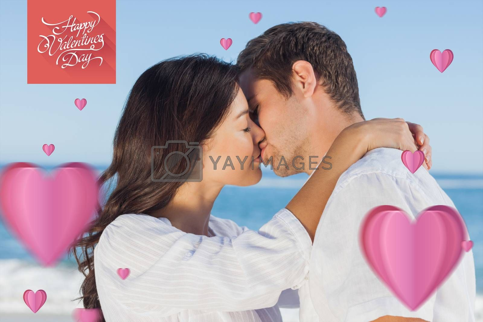 Couple embracing and kissing each other on the beach against happy valentines day