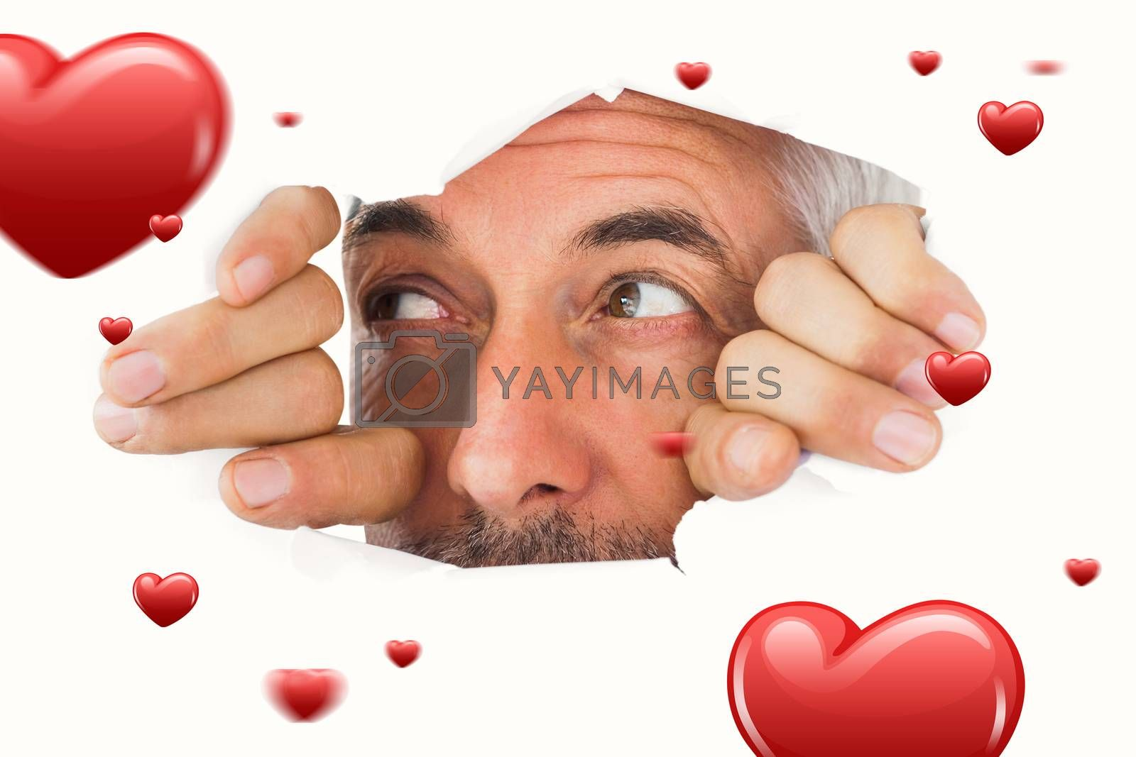 Man looking through torn paper against hearts