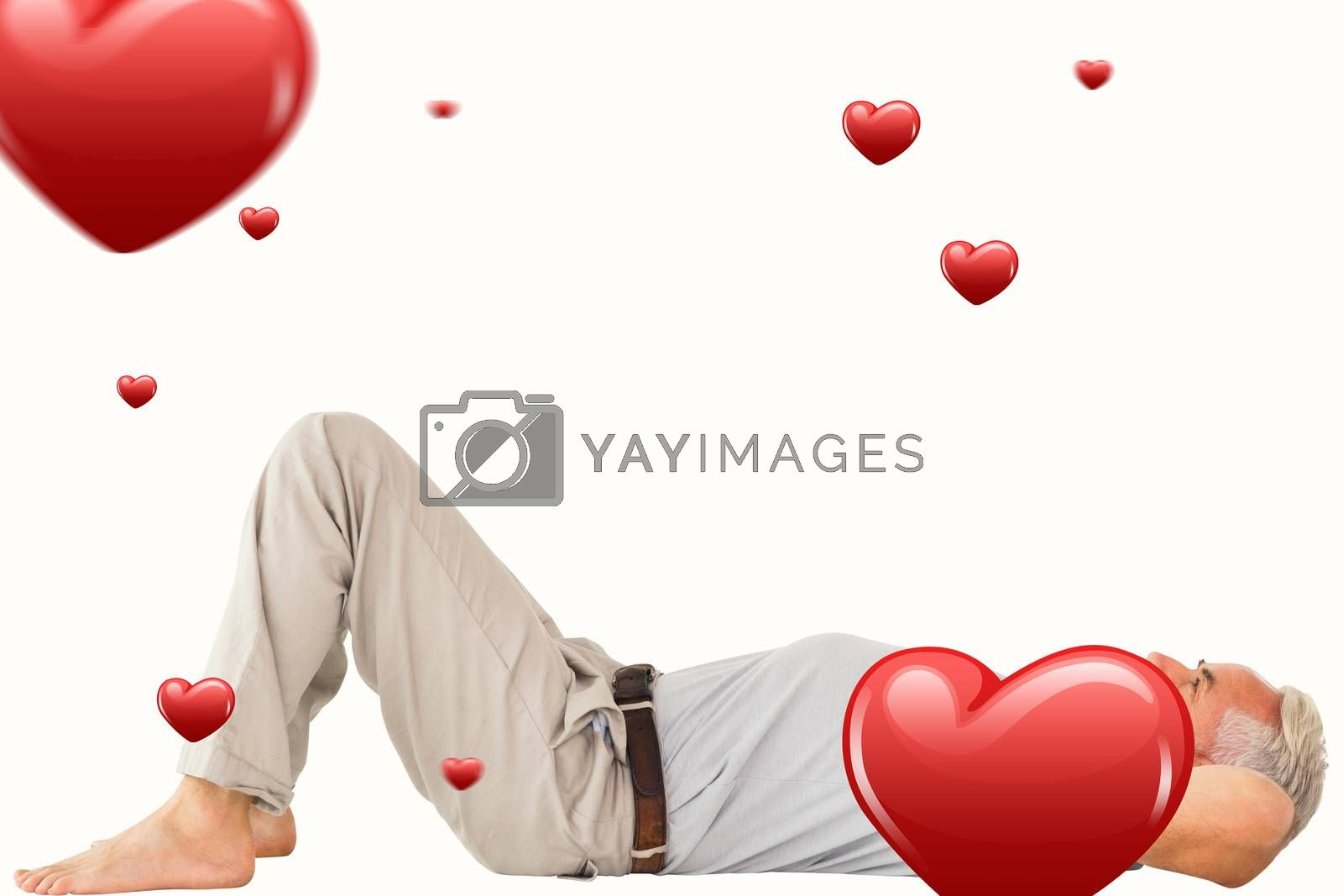 Smiling man lying and looking up against hearts