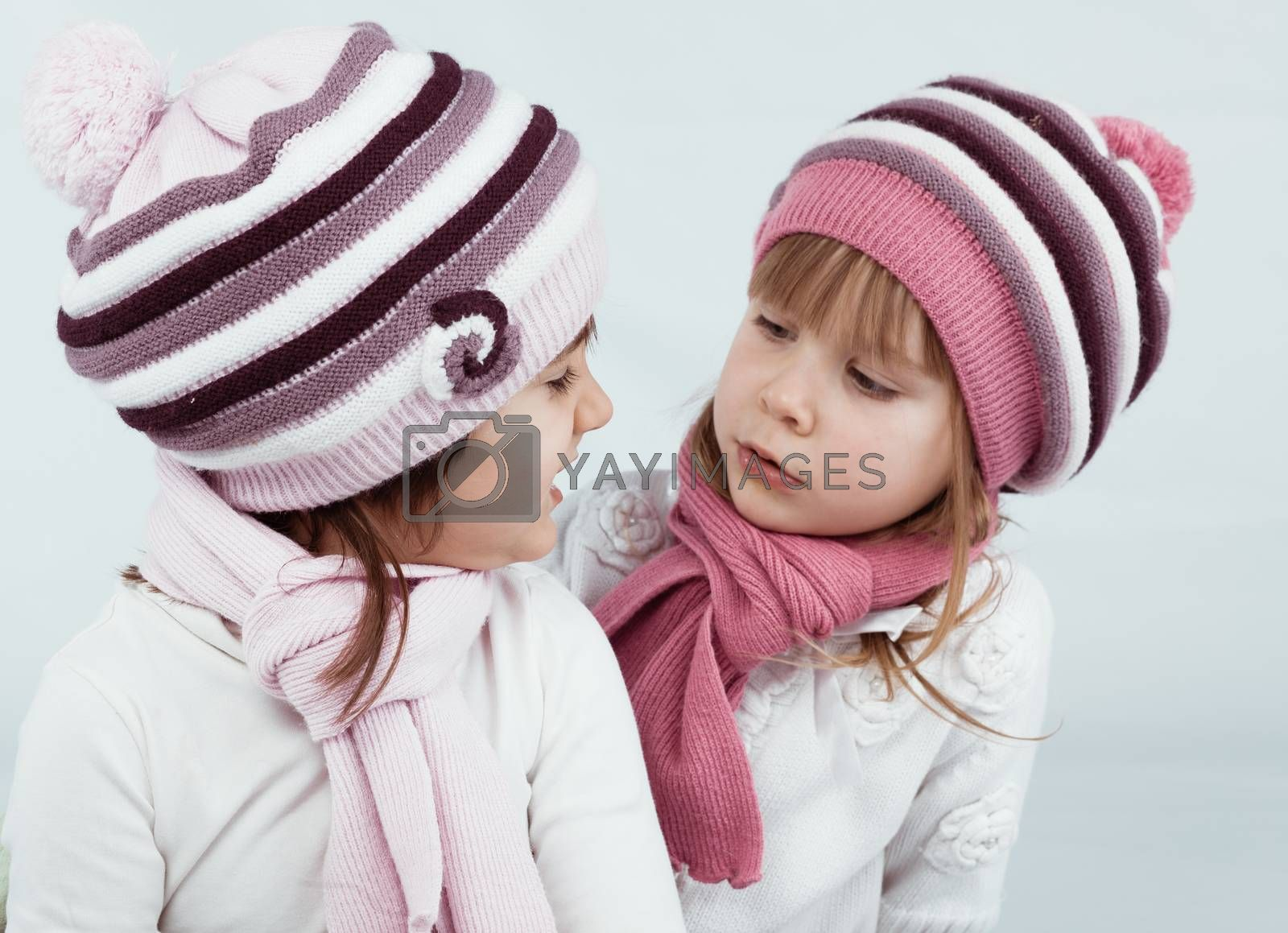 Portrait of two kid girls wearing knitted winter hats and scarves