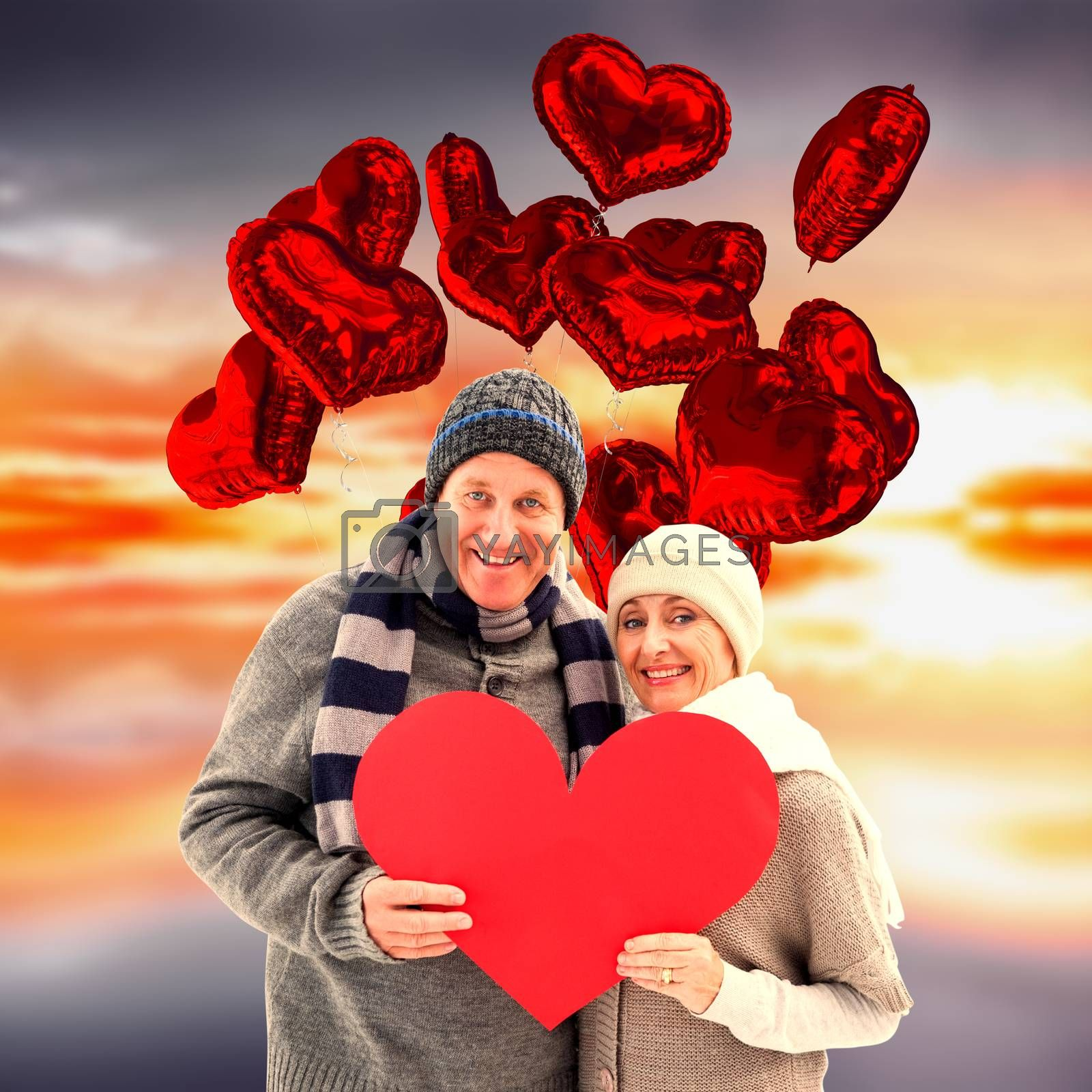 Happy mature couple in winter clothes holding red heart against purple sky with orange clouds