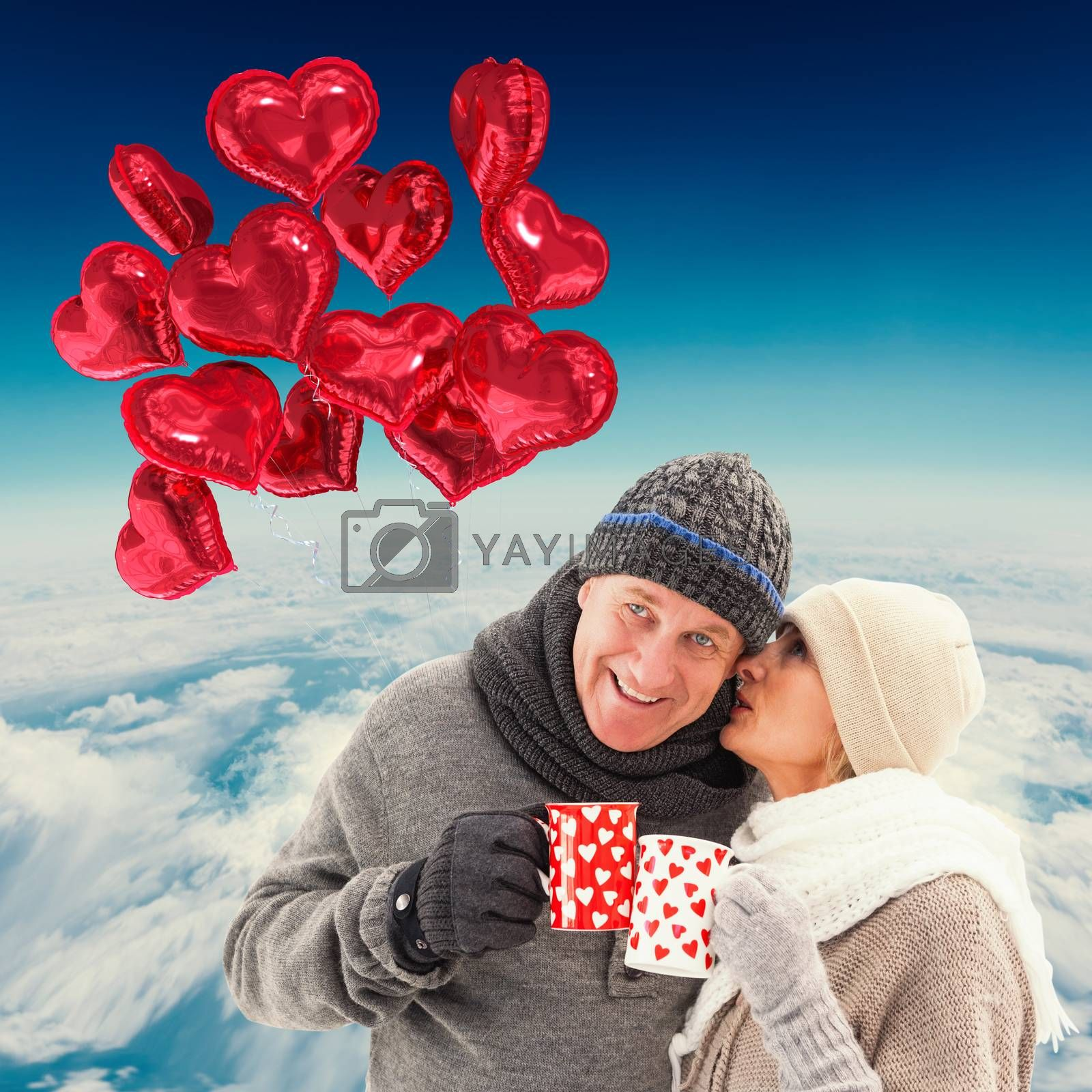 Happy mature couple in winter clothes holding mugs against blue sky over white clouds